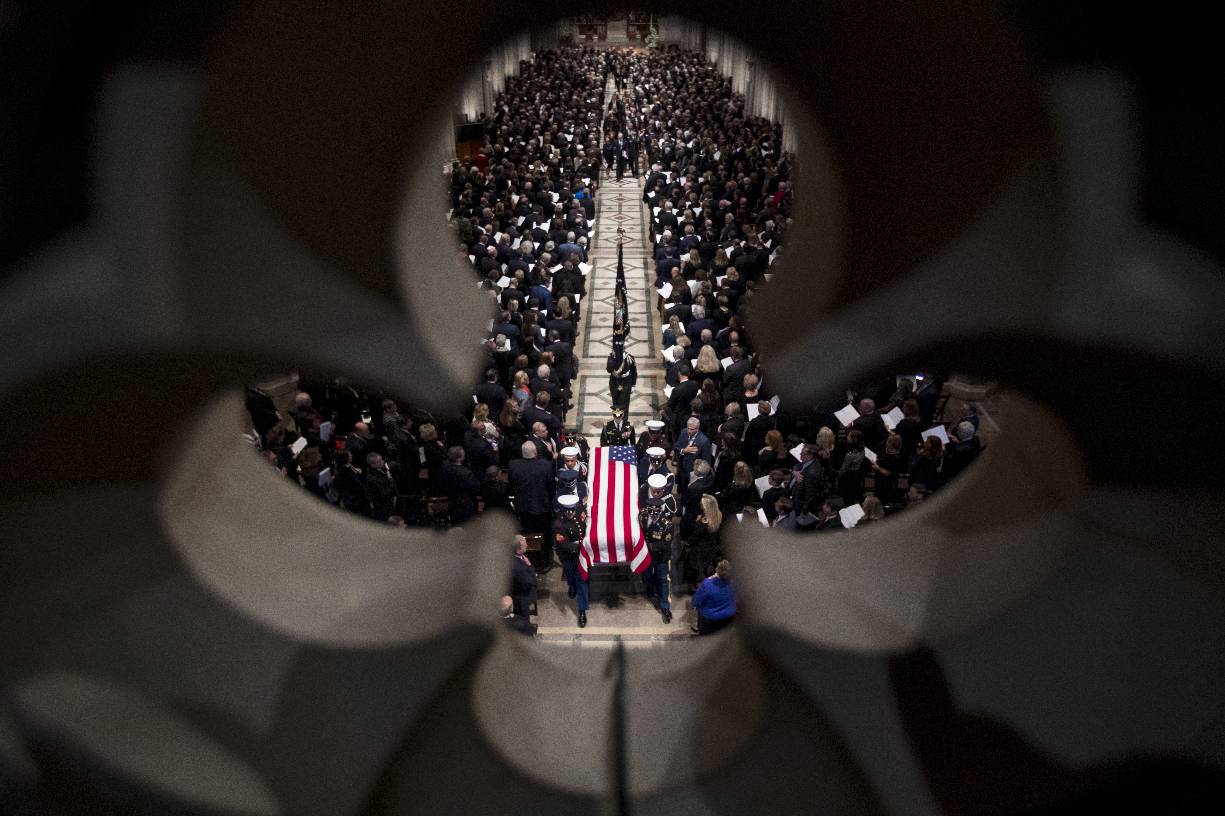 The flag-draped casket of former President George H.W. Bush is carried out by a military honor guard during a State Funeral at the National Cathedral, Wednesday, Dec. 5, 2018, in Washington. (AP Photo/Andrew Harnik, Pool)