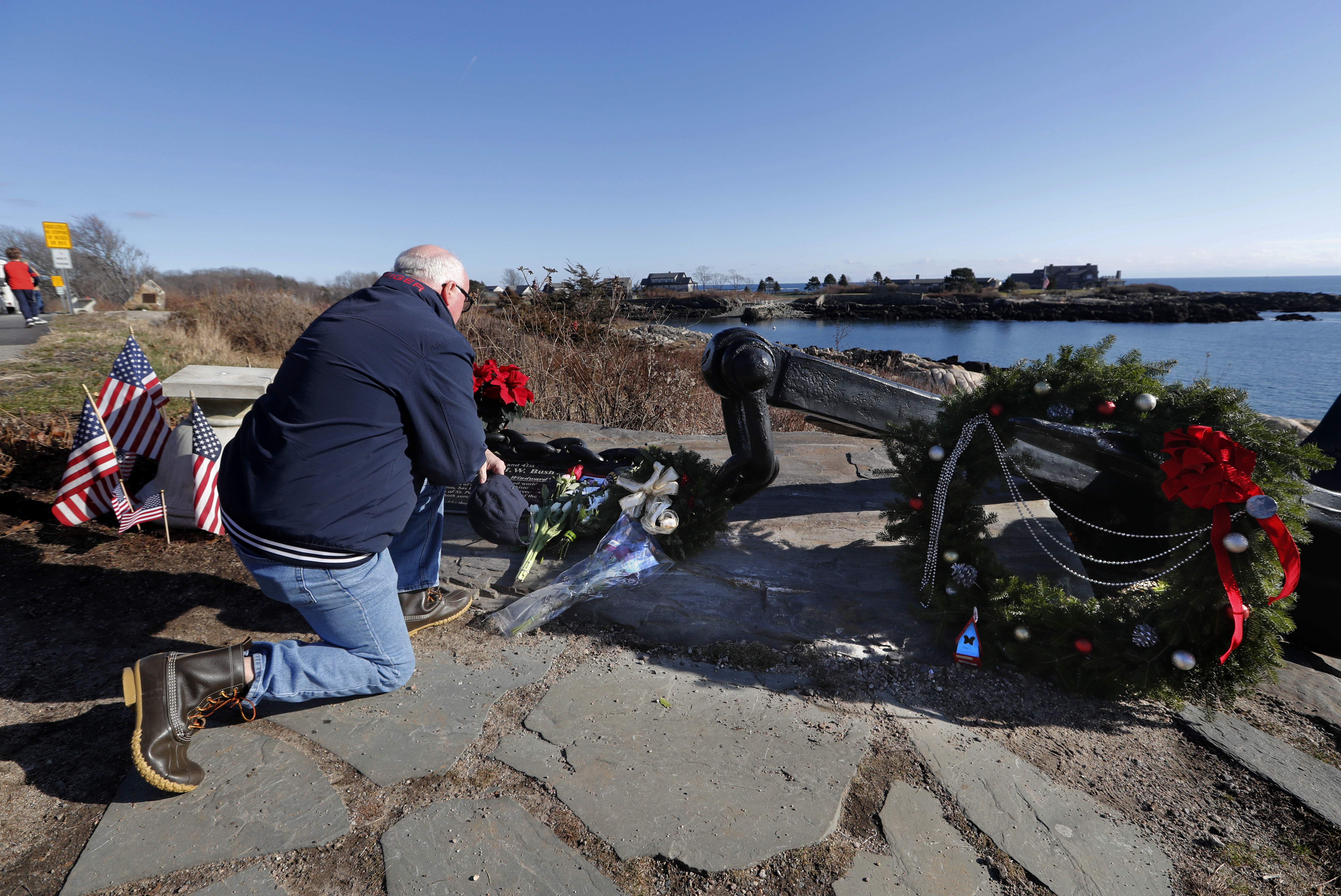 A man pays his respects to former President George H. W. Bush at a makeshift memorial across from Walker's Point, the Bush's summer home, Saturday, Dec. 1, 2018, in Kennebunkport, Maine. (AP Photo/Robert F. Bukaty)