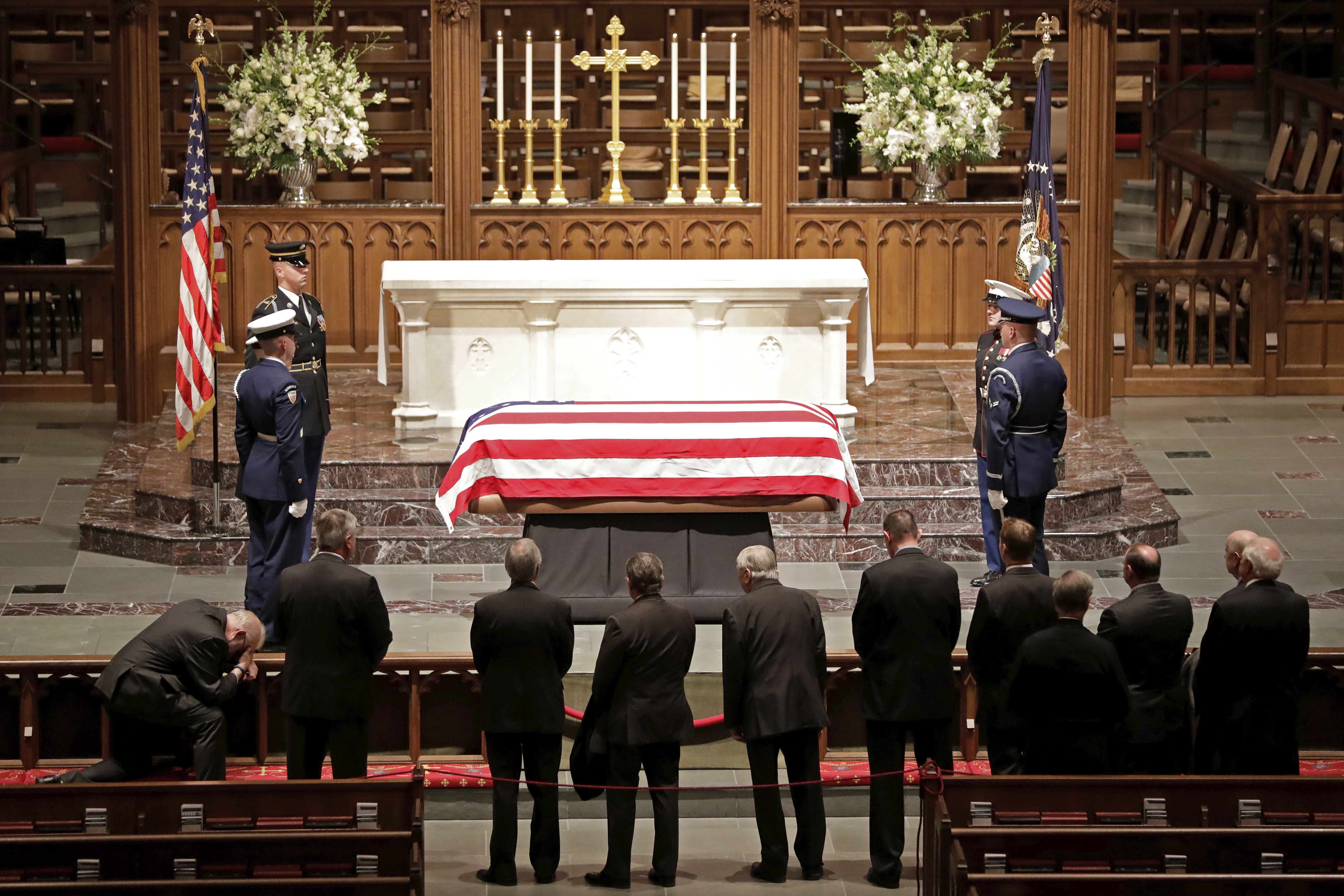 Visitors pay their respects to the flag-draped casket of former President George H.W. Bush at St. Martin's Episcopal Church Wednesday, Dec. 5, 2018, in Houston. (AP Photo/Mark Humphrey)