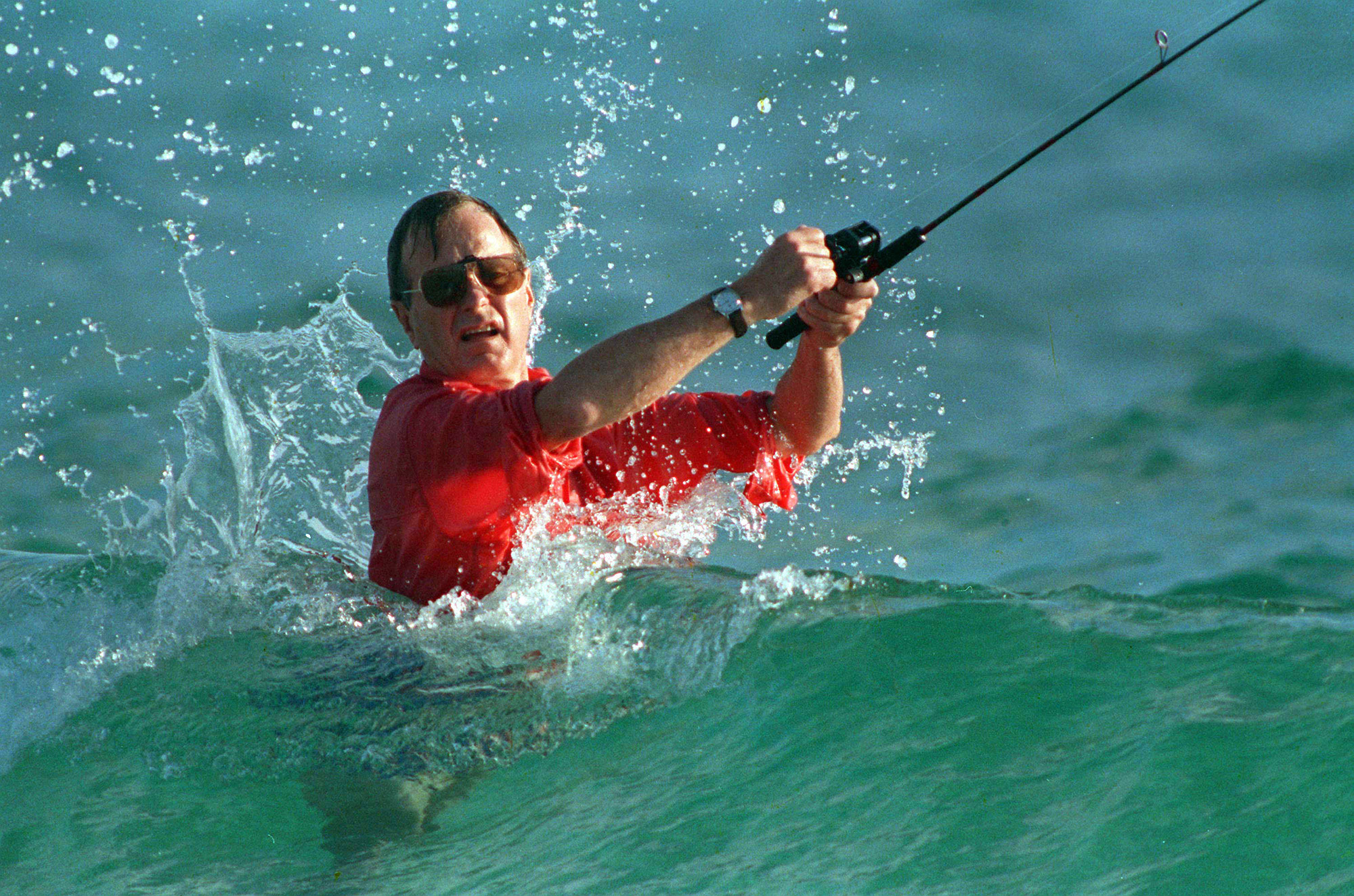 In this Nov. 12, 1988, photo, waves splash on then-President-elect George H.W. Bush as he casts a line while fishing in Gulf Stream, Fla. (AP Photo/Kathy Willens, File)