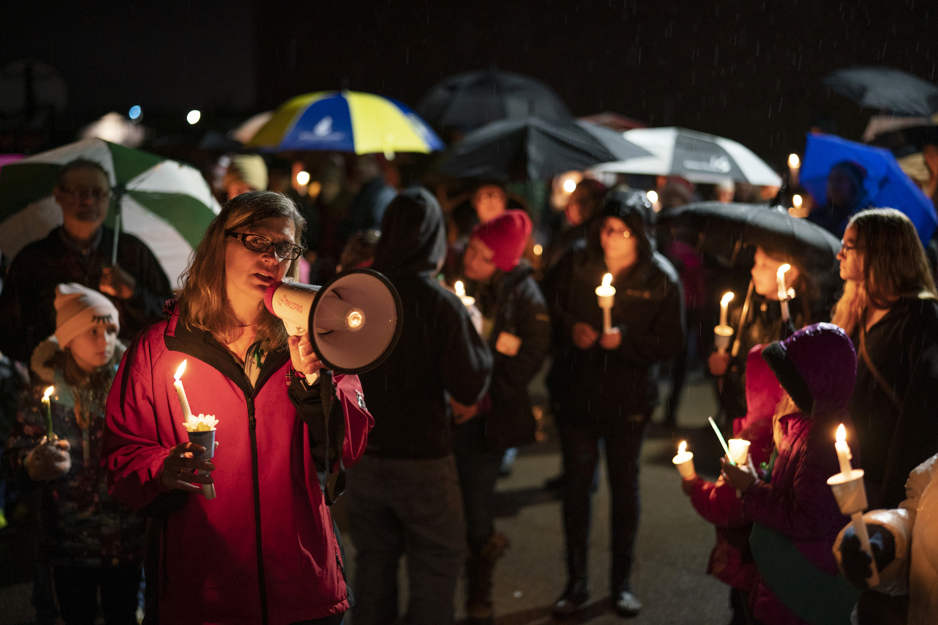 Sherri Jasper, a Girl Scout board member and counselor at Halmstad Elementary School, leads the program for a candlelight vigil at the school in Chippewa Falls, Wis., Sunday evening, Nov. 4, 2018. The western Wisconsin community on Sunday was grieving the deaths of three Girl Scouts and a parent who were collecting trash Saturday along a rural highway when police say a pickup truck veered off the road and hit them before speeding away. The 21-year-old driver, Colten Treu of Chippewa Falls, sped off but later surrendered. He will be charged with four counts of homicide, Lake Hallie police Sgt. Daniel Sokup said. (Jeff Wheeler/Star Tribune via AP)