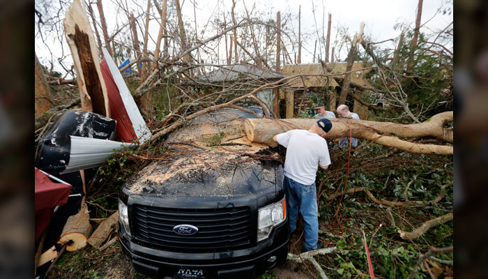 People cut away a tree that'll on a vehicle in the aftermath of Hurricane Michael in Panama City, Fla., Thursday, Oct. 11, 2018