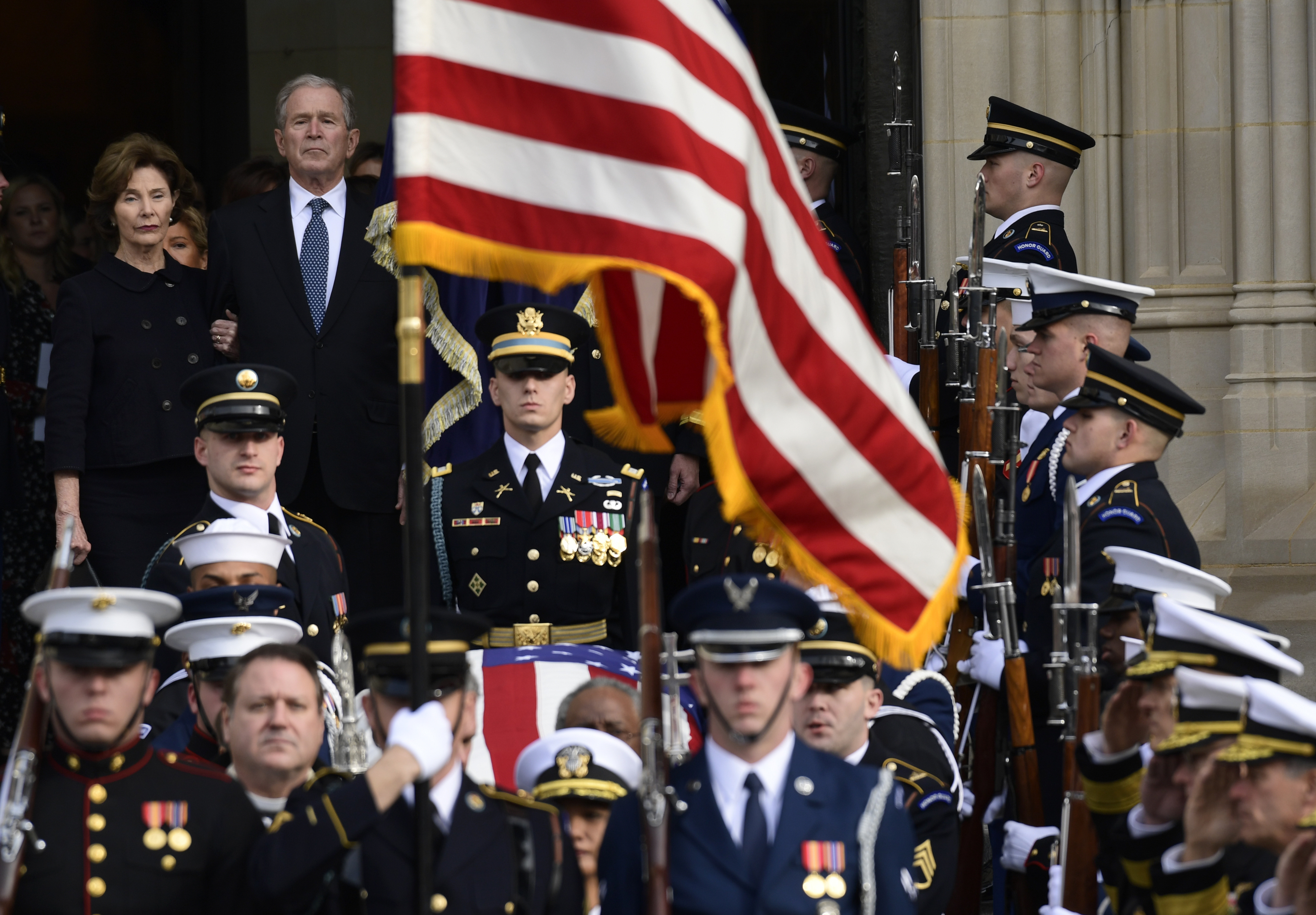 Former President George W. Bush and former first lady Laura Bush, top left, watch as the casket of former President George H.W. Bush is carried out after a State Funeral at the National Cathedral in Washington, Wednesday, Dec. 5, 2018.(AP Photo/Susan Walsh)
