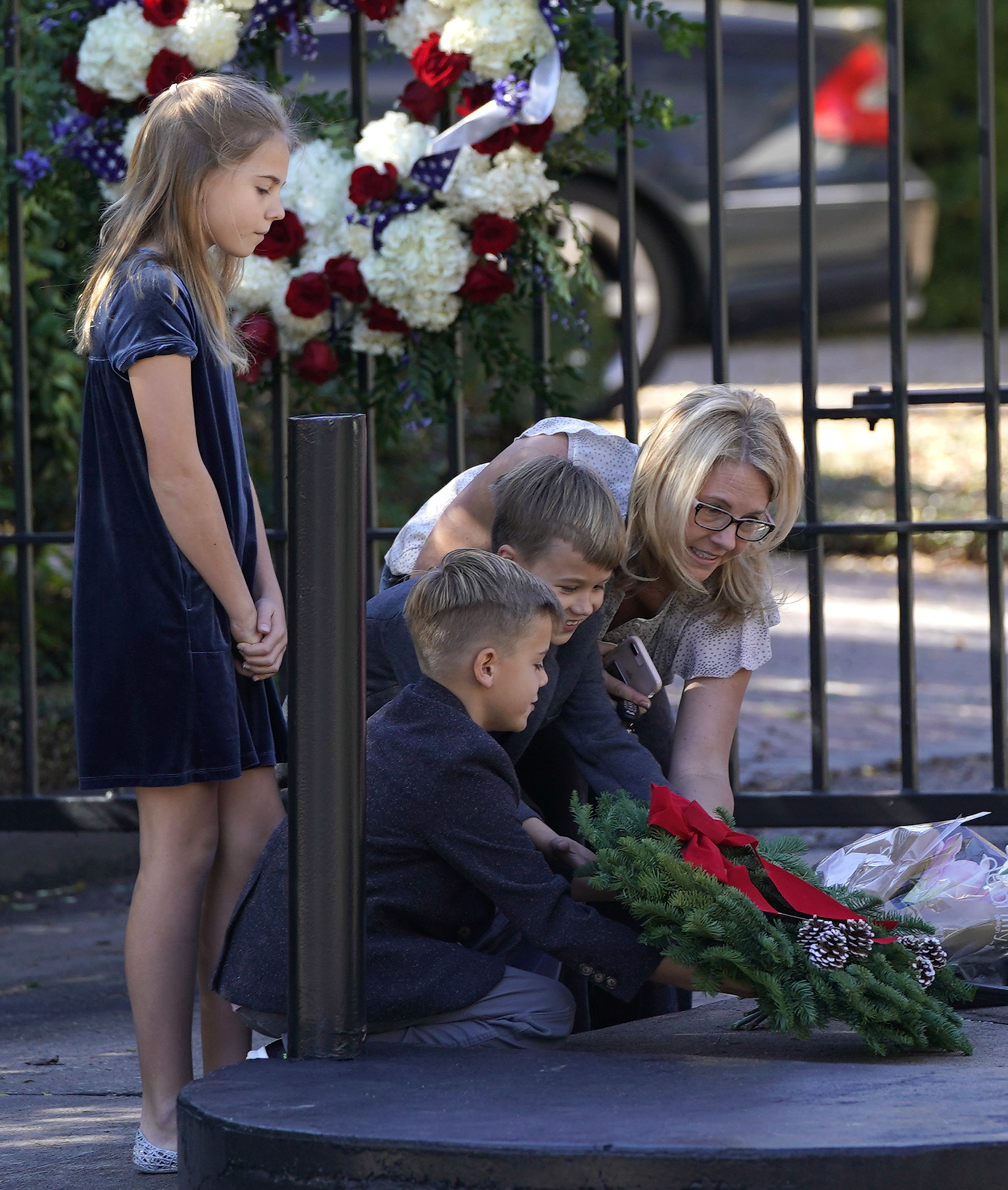 Tiffany Utterson, right, and her children, from left to right, Ella, 11, Ian, 10 and Owen, 8, place a wreath outside the gated community entrance to the home of George H.W. Bush Sunday, Dec. 2, in Houston. (AP Photo/David J. Phillip)