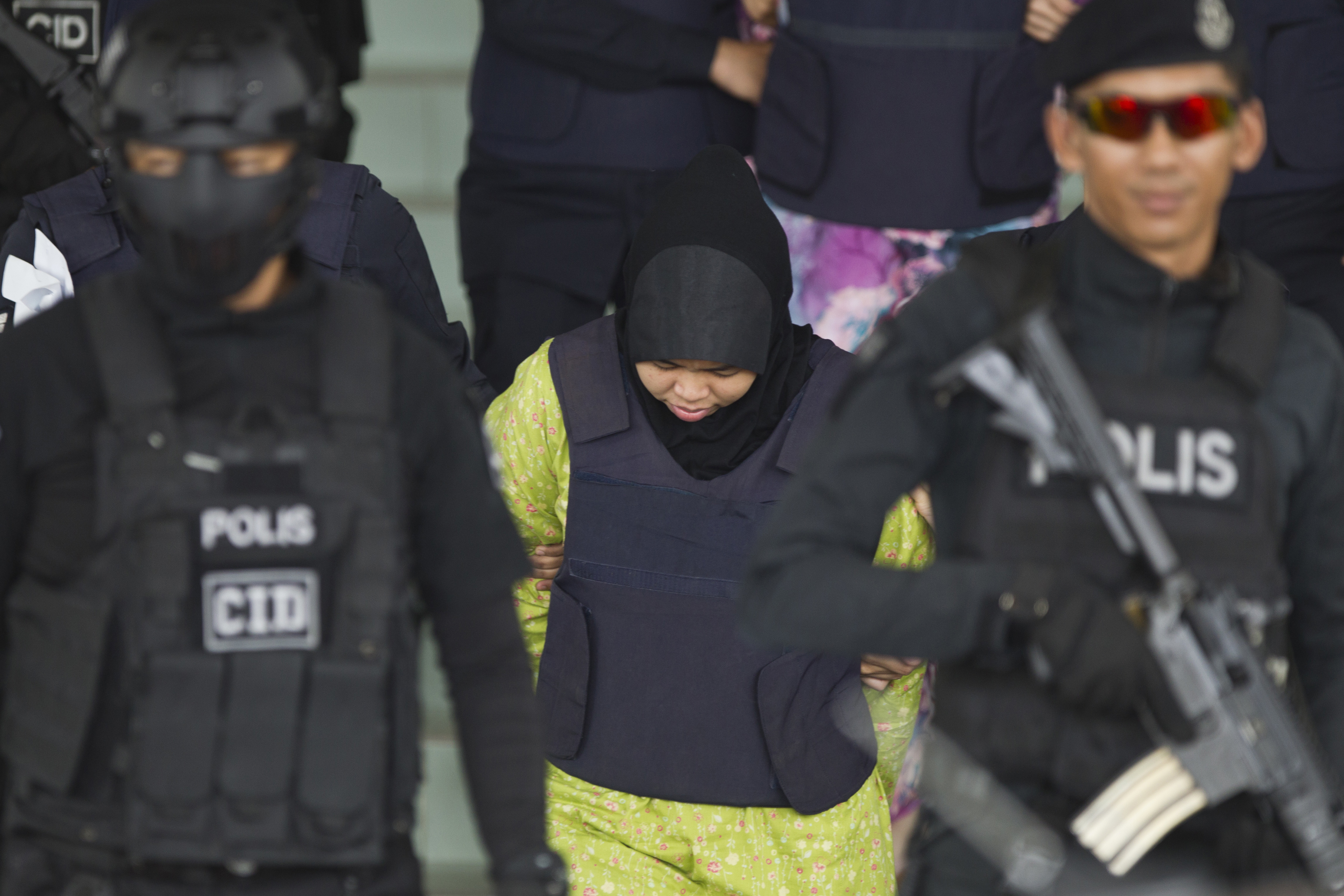 Indonesian Siti Aisyah is escorted by police as she leaves the Shah Alam High Court after a hearing in Shah Alam, Malaysia, Wednesday, Nov. 7, 2018. A Malaysian court on Wednesday set Jan 7 for two Southeast Asian women charged with murdering the North Korean leader's half brother to begin their defense, as their lawyers complained that some witnesses were unreachable. (AP Photo/Yam G-Jun)
