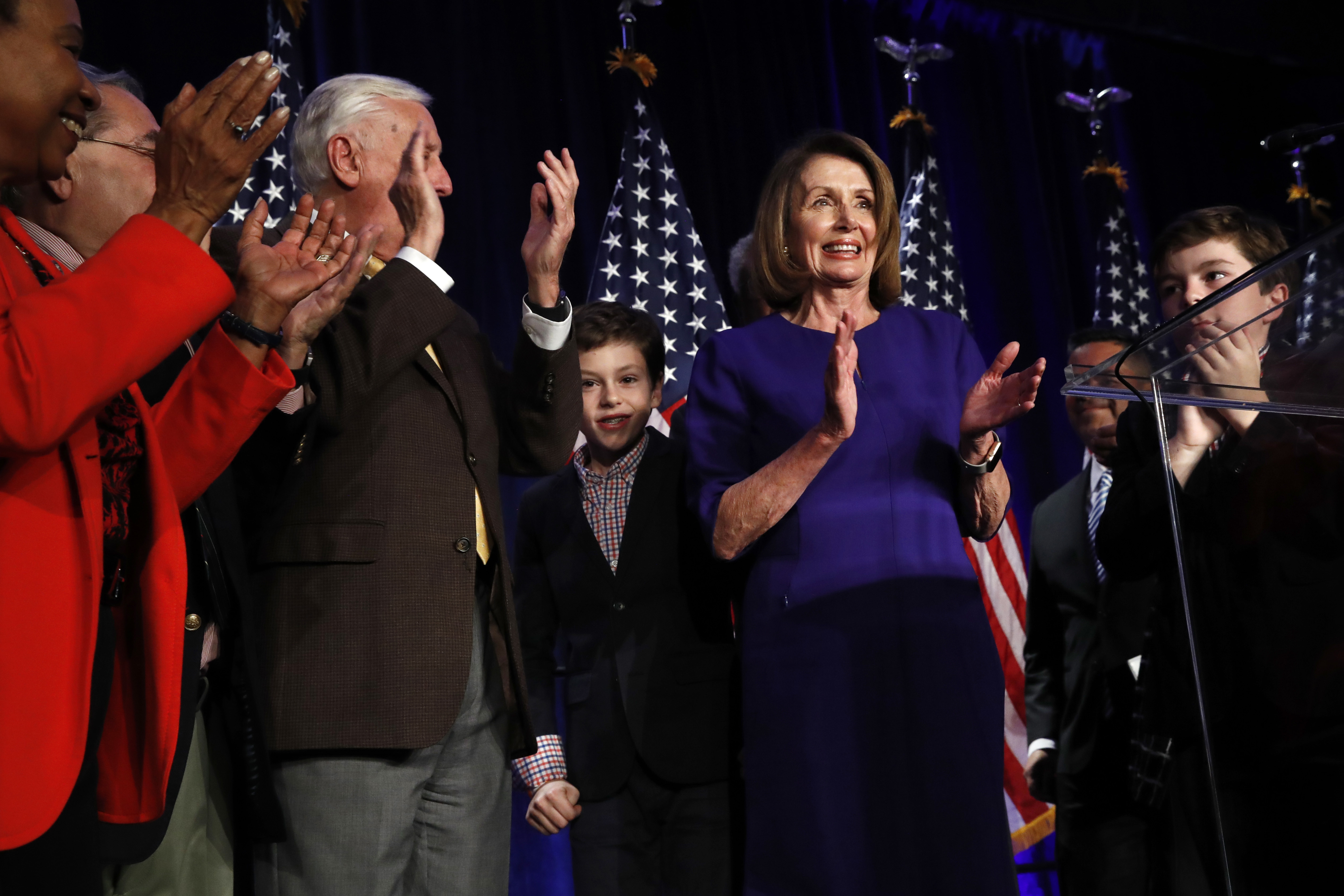 House Democratic Leader Nancy Pelosi of Calif., right, claps between her two grandsons on stage with House Democrats after speaking about Democratic wins in the House of Representatives to a crowd of Democratic supporters during an election night returns event at the Hyatt Regency Hotel, on Tuesday, in Washington. (AP Photo/Jacquelyn Martin)