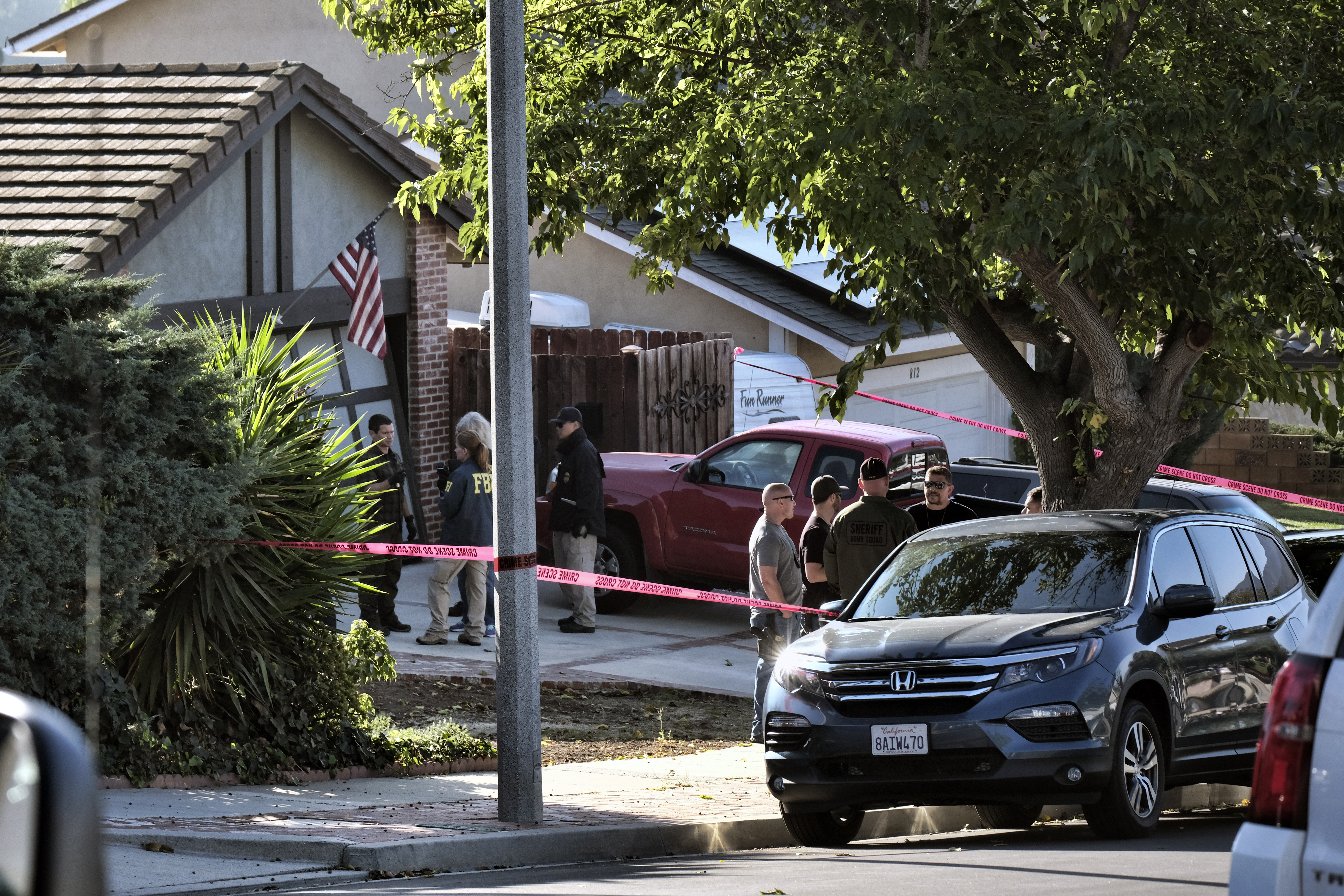 Ventura County Sheriff's deputies and FBI investigators stand outside the house of shooting suspect David Ian Long in Newbury Park, Calif., on Thursday, Nov. 8, 2018. Authorities said the former Marine opened fire at a country music bar in Southern California on Wednesday evening. (AP Photo/Richard Vogel)