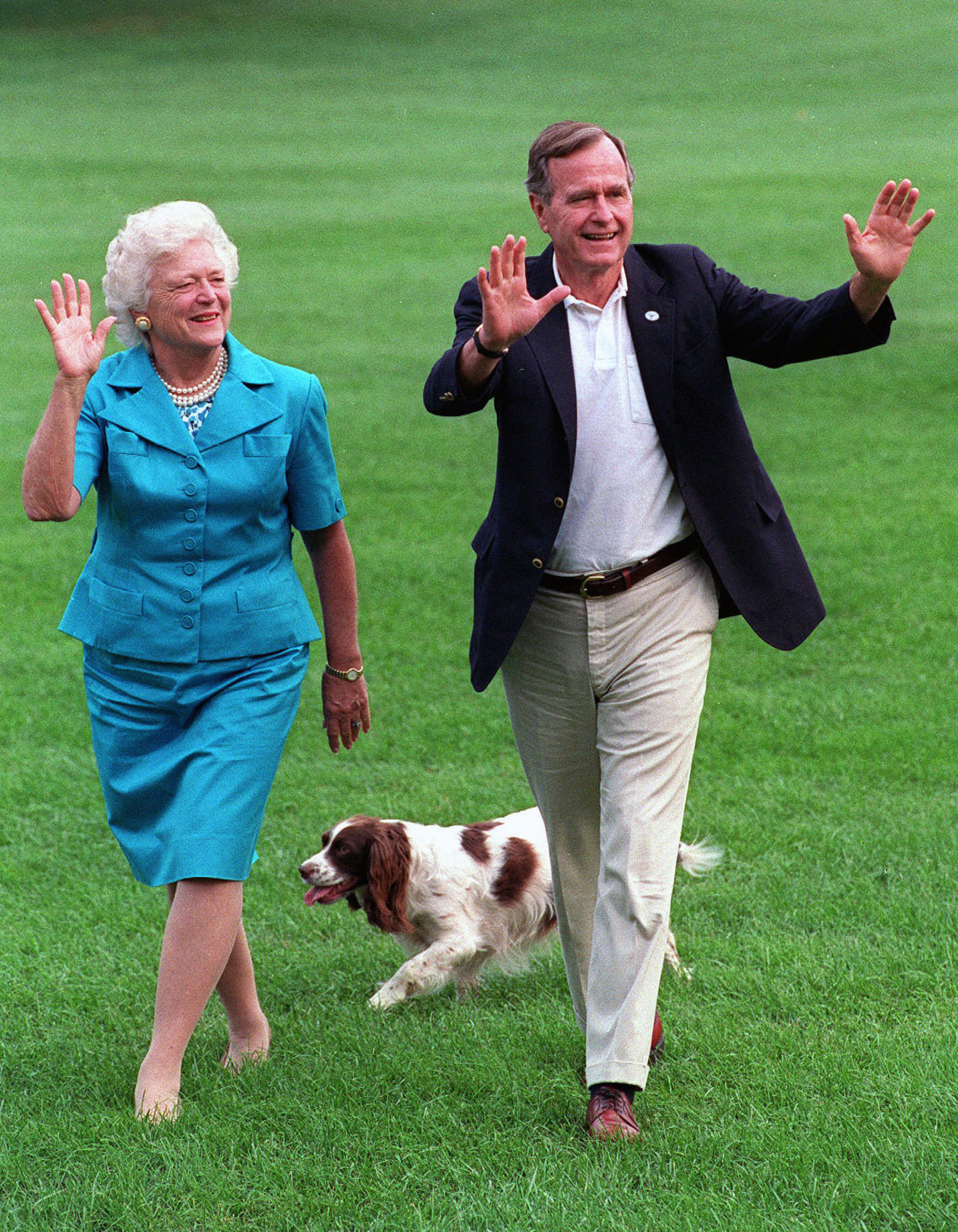 In this Aug. 24, 1992, photo, President George H.W. Bush and first lady Barbara Bush walk with their dog Millie across the South Lawn as they return to the White House. (AP Photo/Scott Applewhite, File)
