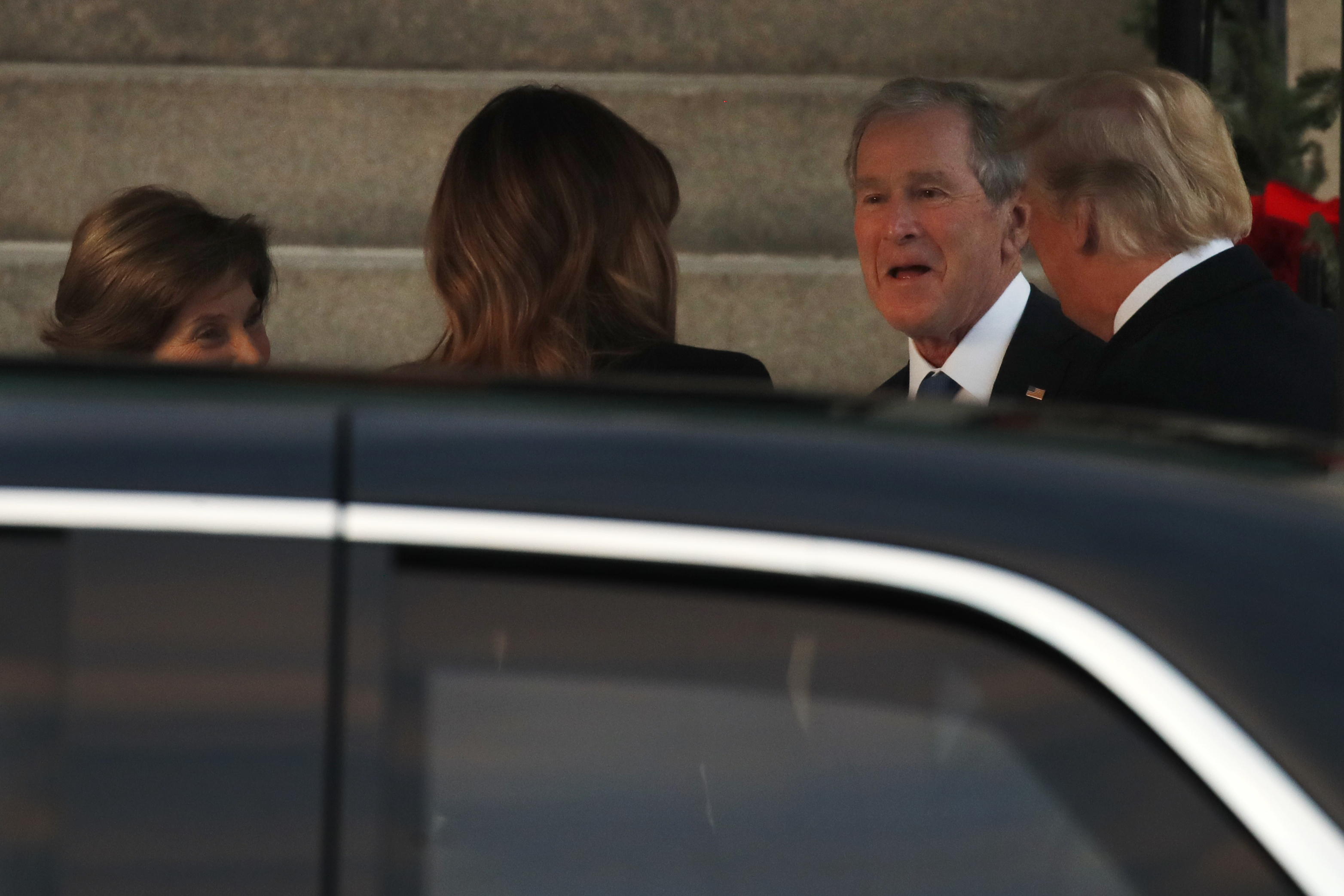 President Donald Trump, right, and first lady Melania Trump, arrive at Blair House and are greeted by former President George W. Bush and former first lady Laura Bush, Tuesday, Dec. 4, 2018, in Washington. (AP Photo/Jacquelyn Martin)
