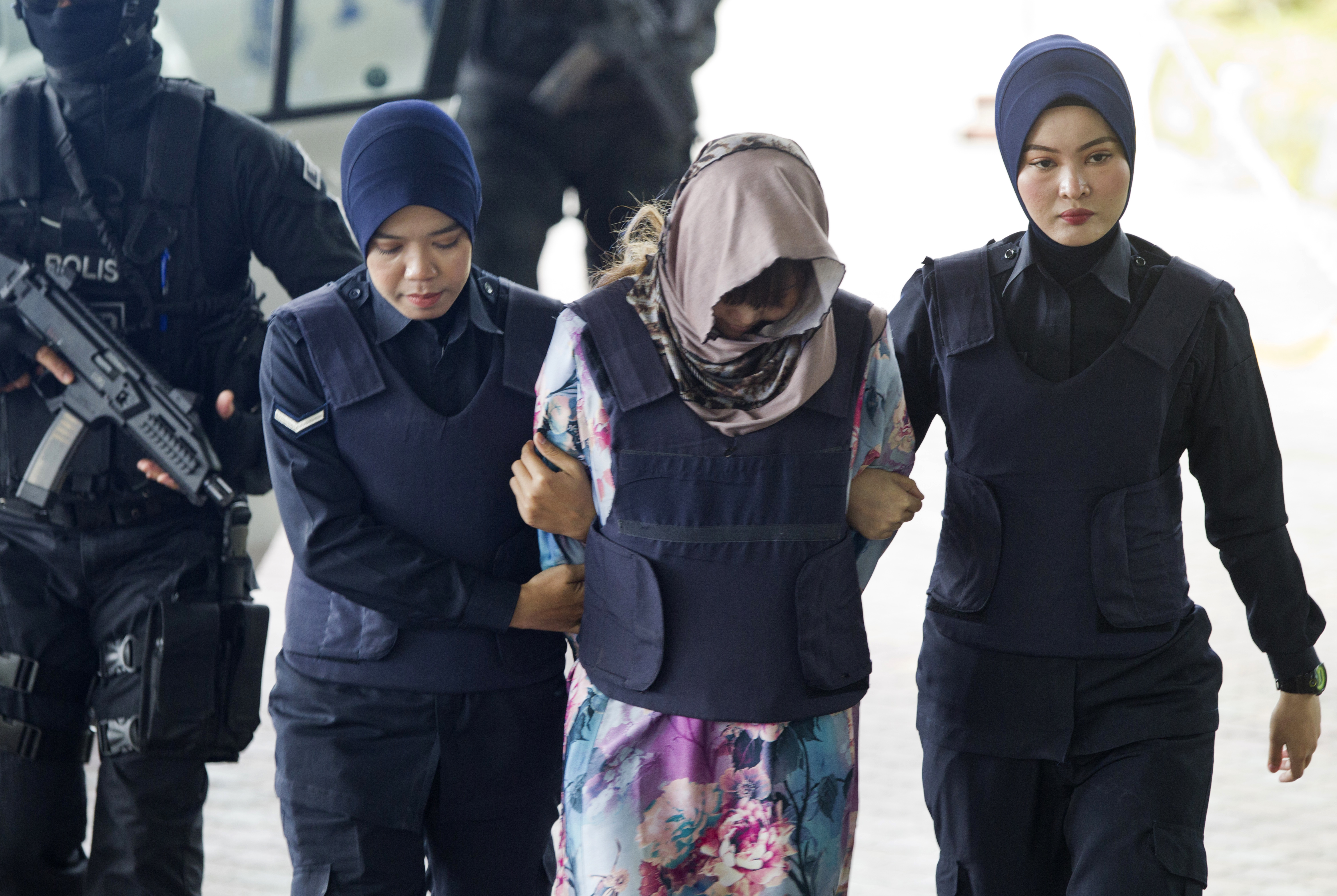 Vietnamese Doan Thi Huong is escorted by police as she arrives for a court hearing at Shah Alam High Court in Shah Alam, Malaysia, Wednesday, Nov. 7, 2018. The two woman, Doang and Indonesian Siti Aisyah, arrived at court for case management after Malaysian court has ordered them to enter their defense over the murder of north Korean leader's half brother in an assassination that has gripped the world. (AP Photo/Yam G-Jun)
