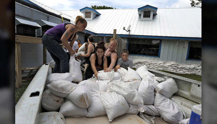 Krystal Day, of Homosassa, Fla., left, leads a sandbag assembly line at the Old Port Cove restaurant Tuesday, Oct. 9 in Ozello, FL. Employees were hoping to protect the restaurant from floodwaters as Hurricane Michael continues to churn in the Gulf of Mexico heading for the Florida panhandle. (AP Photo/Chris O'Meara)