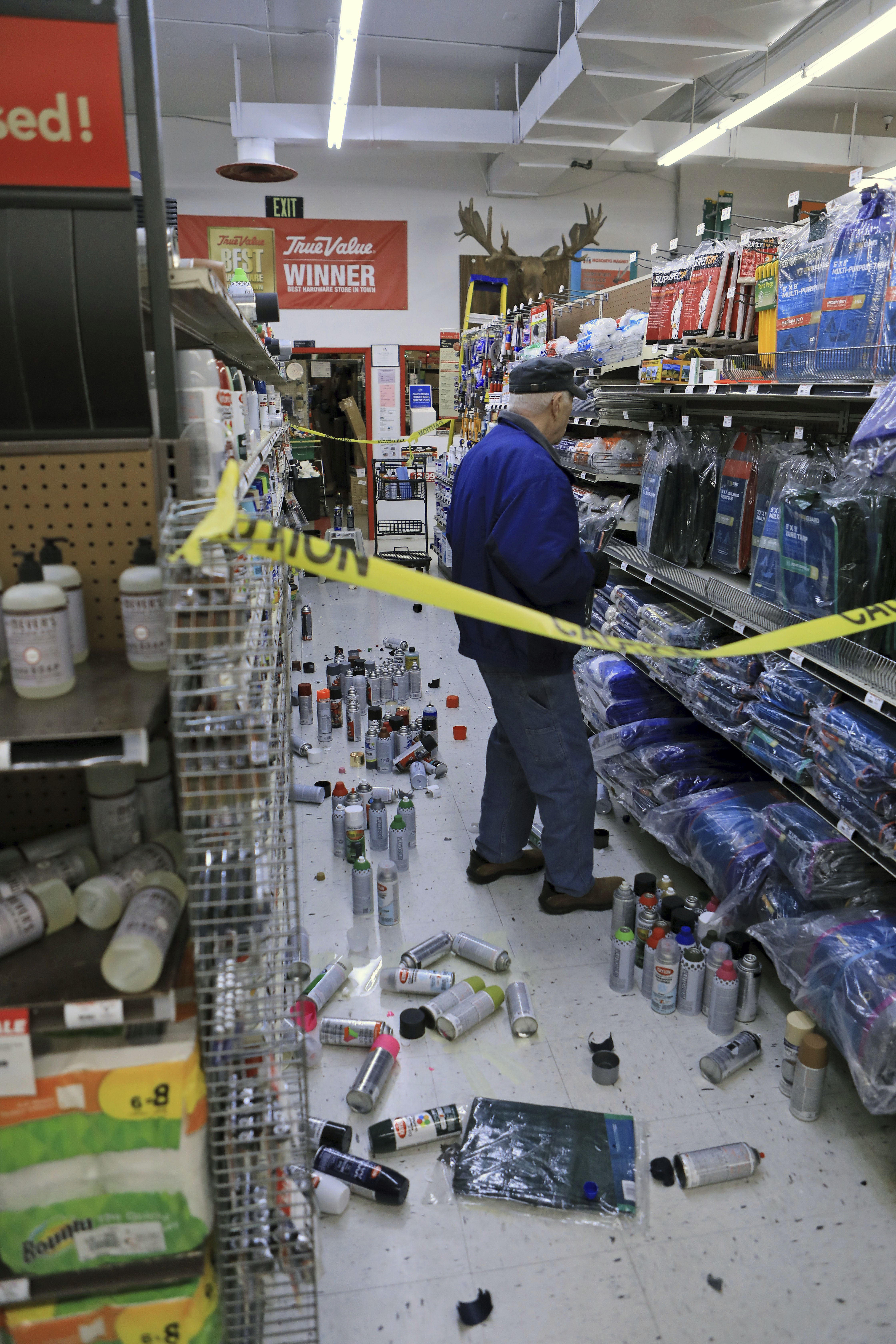 A customer at Anchorage True Value hardware store shops in the partially cleaned-up paint aisle after an earthquake Friday morning, Nov. 30, 2018, in Anchorage, Alaska. Tim Craig, owner of the south Anchorage store, said no one was injured but hundreds of items hit the floor and two shelves collapsed in a stock room. (AP Photo/Dan Joling)