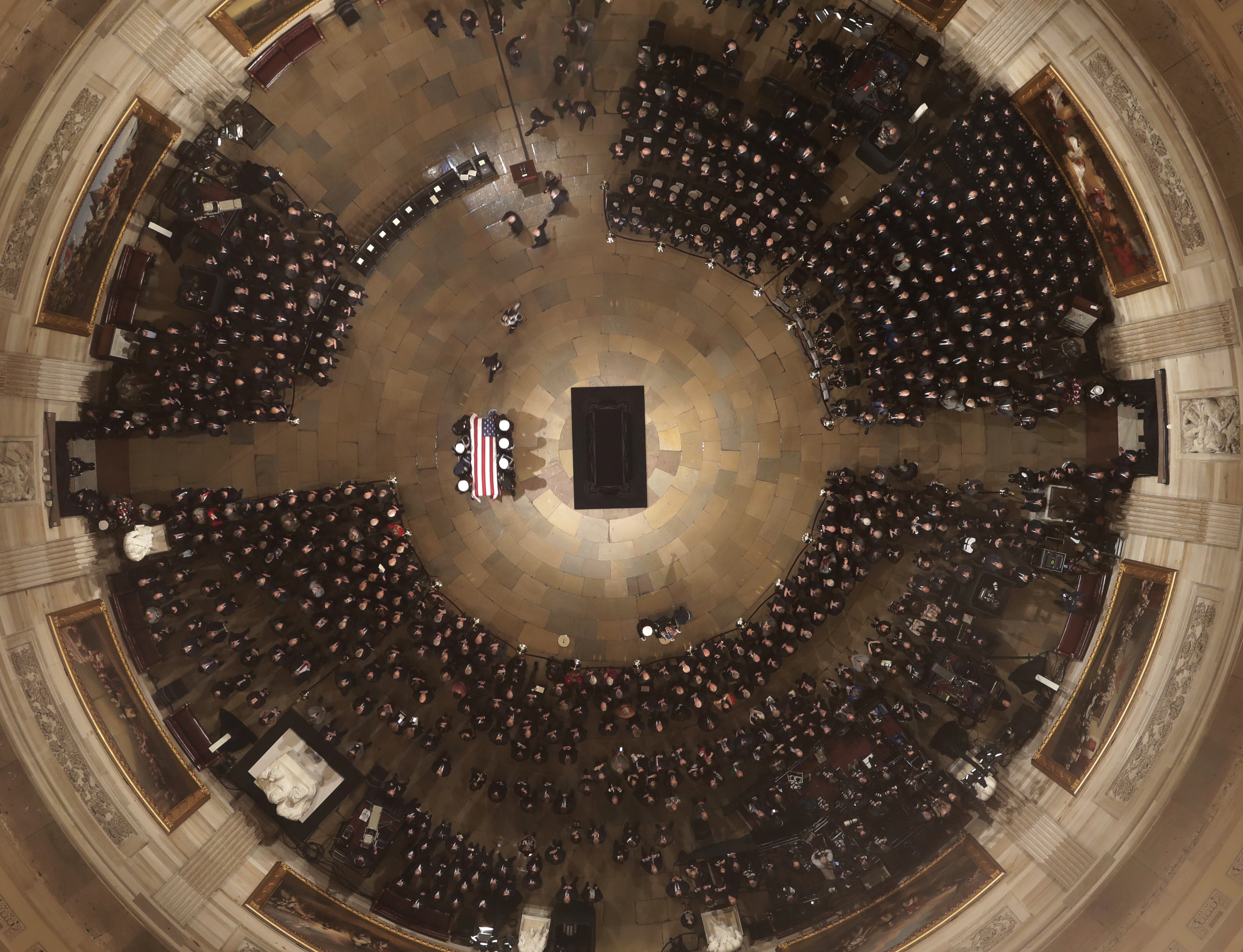 The flag-draped casket of former President George H.W. Bush is carried by a joint services military honor guard into the U.S. Capitol Rotunda Monday, Dec. 3, 2018, in Washington.