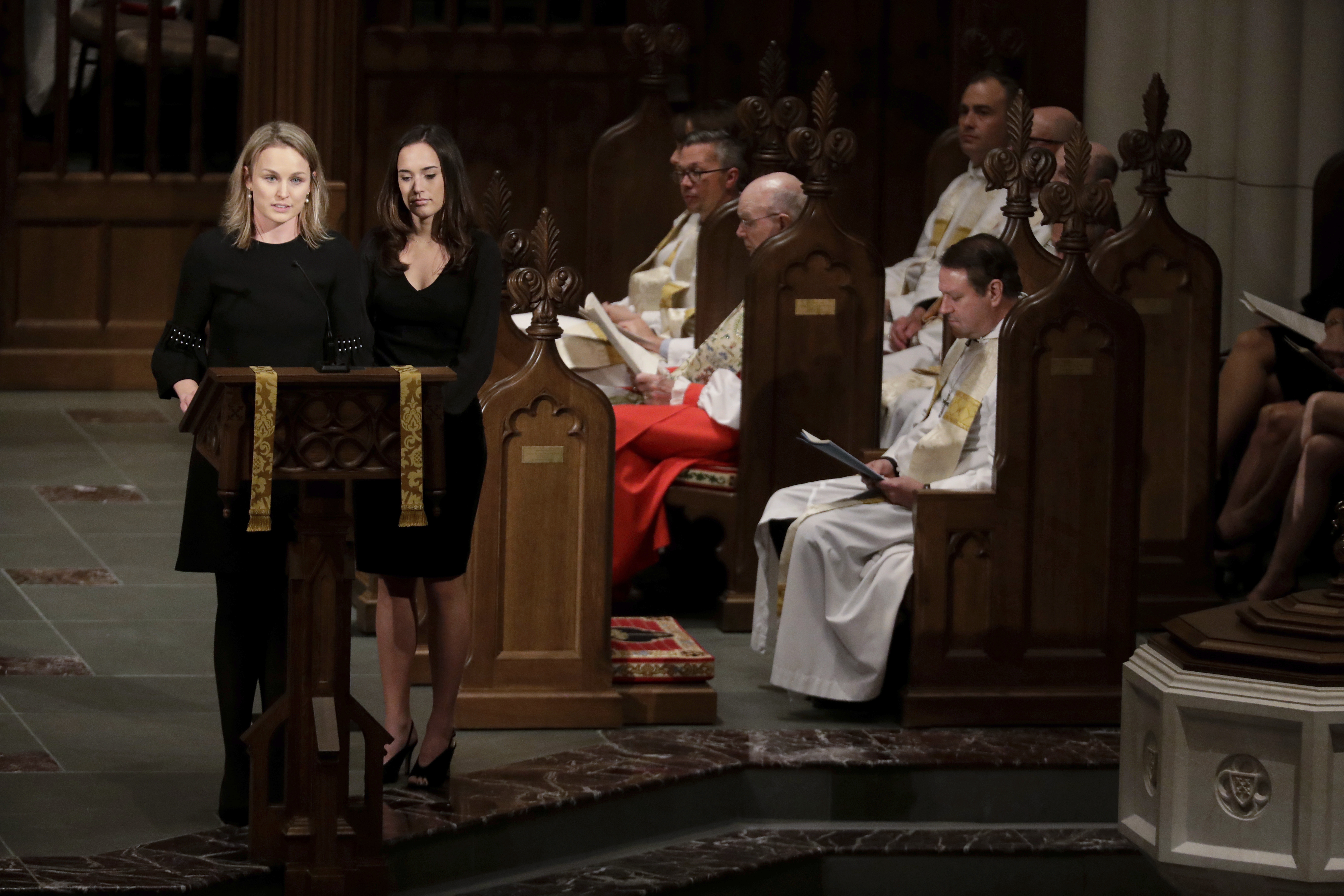 Granddaughters Nancy Ellis LeBlond Sosa, left, and Georgia Grace Koch, read scripture during a funeral for former President George H.W. Bush at St. Martin's Episcopal Church Thursday, Dec. 6, 2018, in Houston. (AP Photo/Mark Humphrey)
