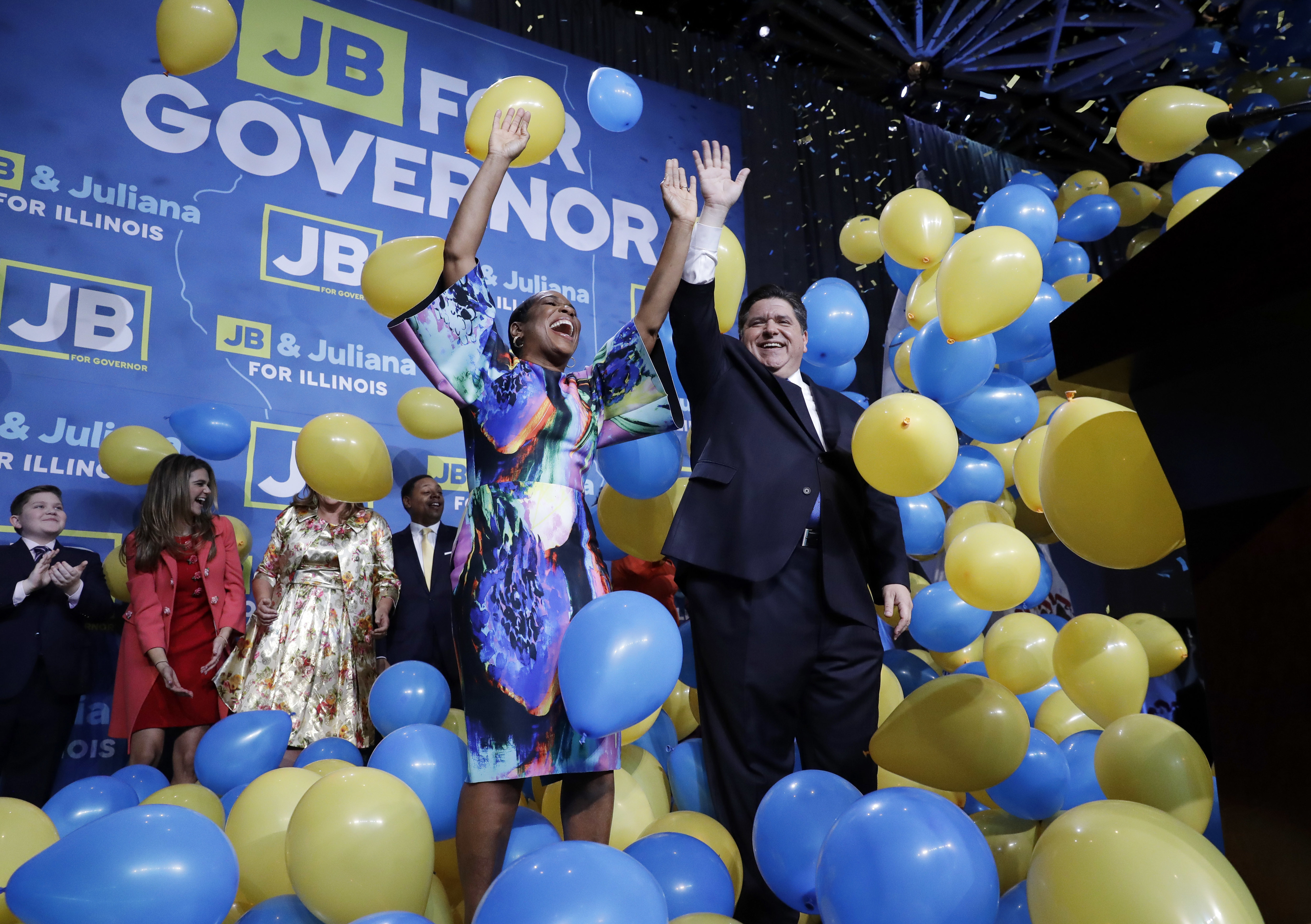 Democratic gubernatorial candidate J.B. Pritzker, right, and his running mate Lt. Governor candidate Juliana Stratton celebrate as they wave to supporters after Pritzker is elected as Illinois governor over Republican incumbent Bruce Rauner in Chicago, Tuesday, Nov. 6, 2018. (AP Photo/Nam Y. Huh)