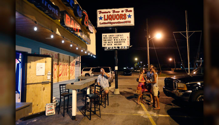 Patrons who so far have chosen not to evacuate gather at Buster's Beer & Bait for drinks, in Panama City Beach, FL., Tuesday, Oct. 9. Despite officials' warning about the storm's severity, some chose not to evacuate. (AP Photo/Gerald Herbert)