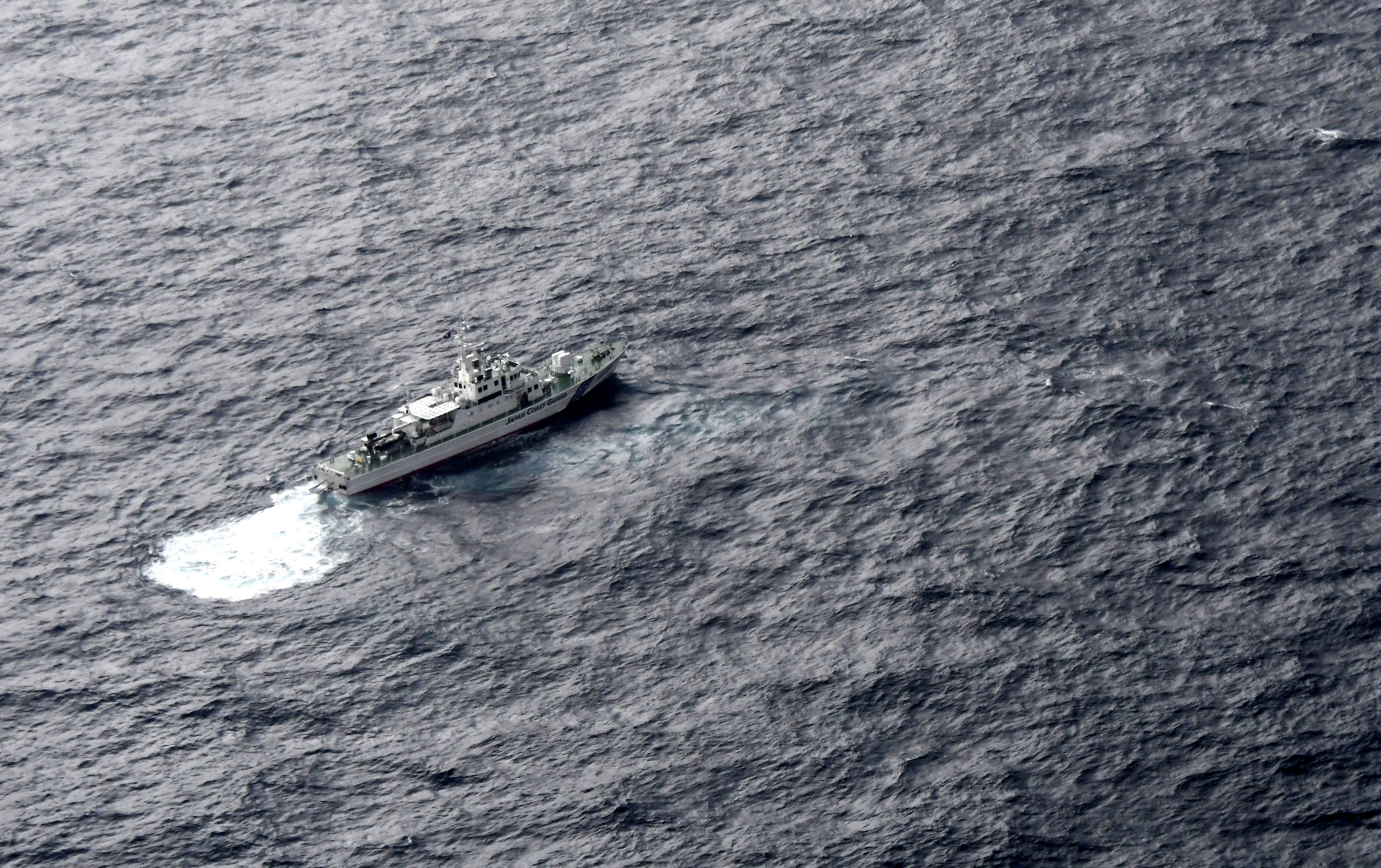 In this aerial photo, Japan's Coast Guard ship is seen at sea during a search operation for U.S. Marine refueling plane and fighter jet off Muroto, Kochi prefecture, southwestern Japan, Thursday, Dec. 6, 2018. A Marine refueling plane and a fighter jet crashed into the Pacific Ocean off Japan's southwestern coast after a midair collision early Thursday, and rescuers found one of the seven crew members in stable condition while searching for the others, officials said. The U.S. Marine Corps said that the 2 a.m. crash involved an F/A-18 fighter jet and a KC-130 refueling aircraft during regular training after the planes took off from their base in Iwakuni, near Hiroshima in western Japan. (Kyodo News via AP)
