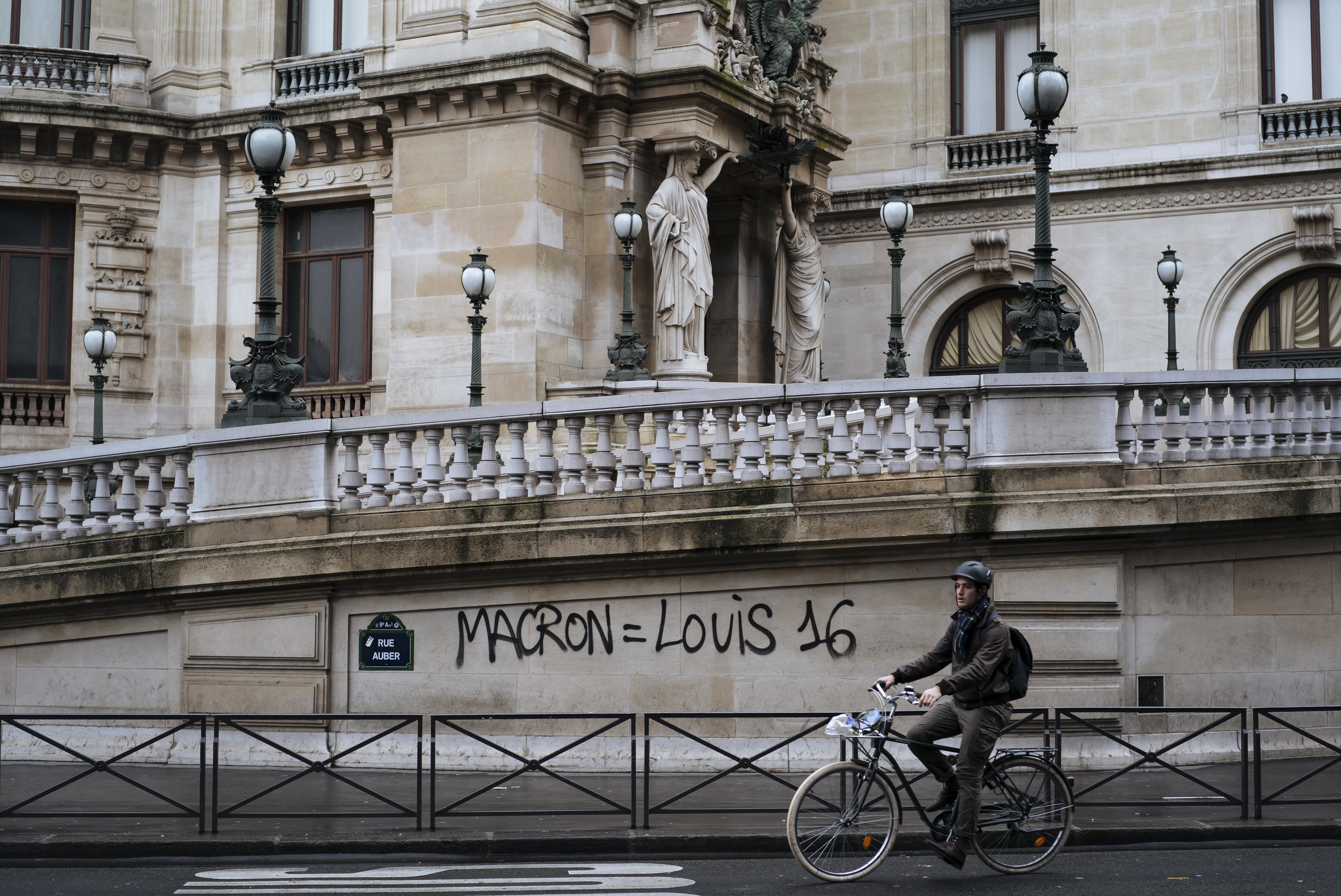 A man rides his bicycle past by a graffiti reading