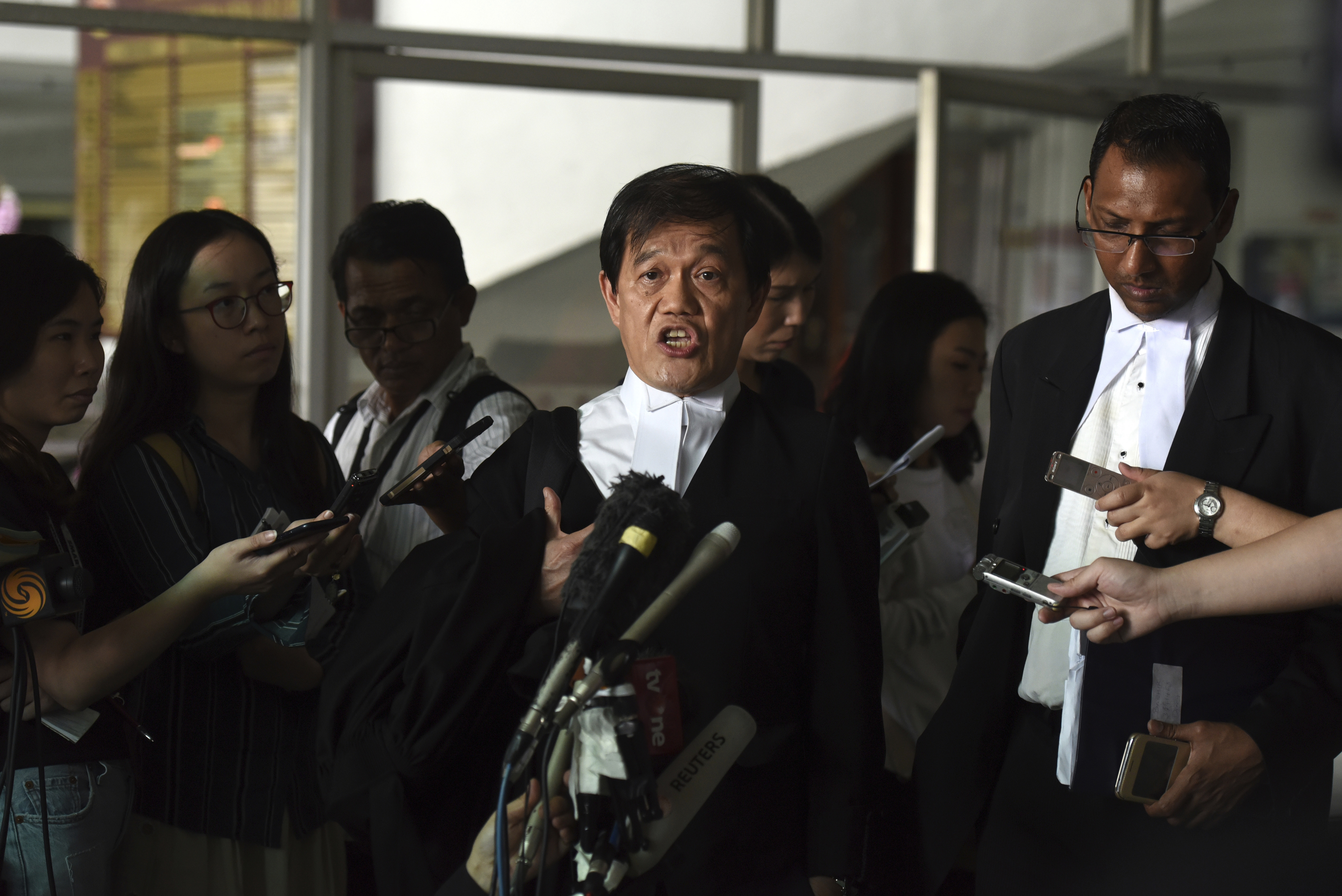 Hisyam Teh Poh Teik, center, the lawyer for Vietnamese Doan Thi Huong, speaks to the media after a court hearing at the Shah Alam High Court after a hearing in Shah Alam, Malaysia, Wednesday, Nov. 7, 2018. A Malaysian court on Wednesday set Jan 7 for two Southeast Asian women charged with murdering the North Korean leader's half-brother to begin their defense, as their lawyers complained that some witnesses were unreachable. (AP Photo/Yam G-Jun)