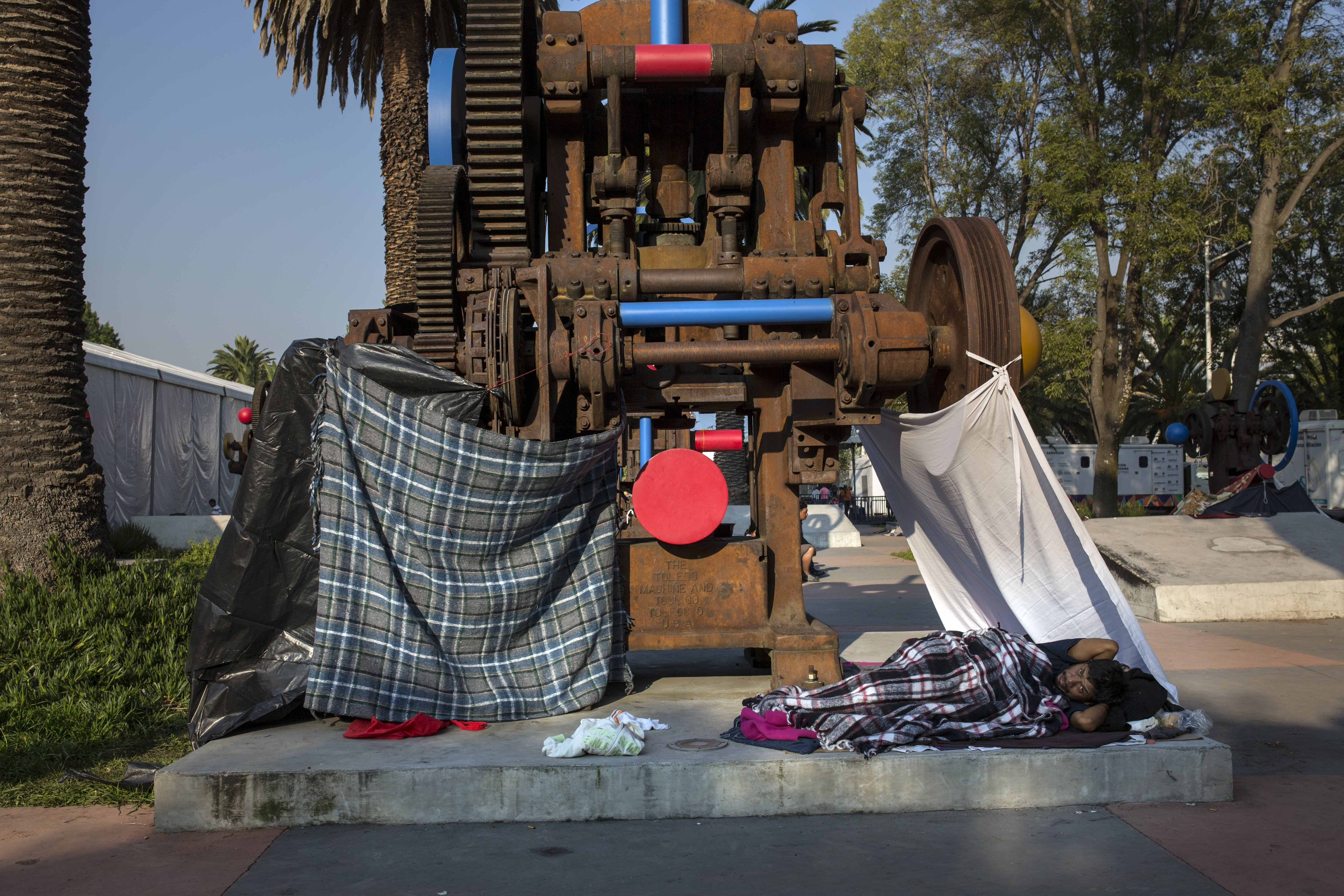 Juan Antonio Ortiz, 38, from Guatemala, rests in a makeshift shelter at the Jesus Martinez stadium in Mexico City, Wednesday, Nov. 7, 2018. Central American migrants on Wednesday continued to straggle in for a rest stop at a Mexico City stadium, where about 4,500 continue to weigh offers to stay in Mexico against the desire of many to reach the U.S. border. (AP Photo/Rodrigo Abd)
