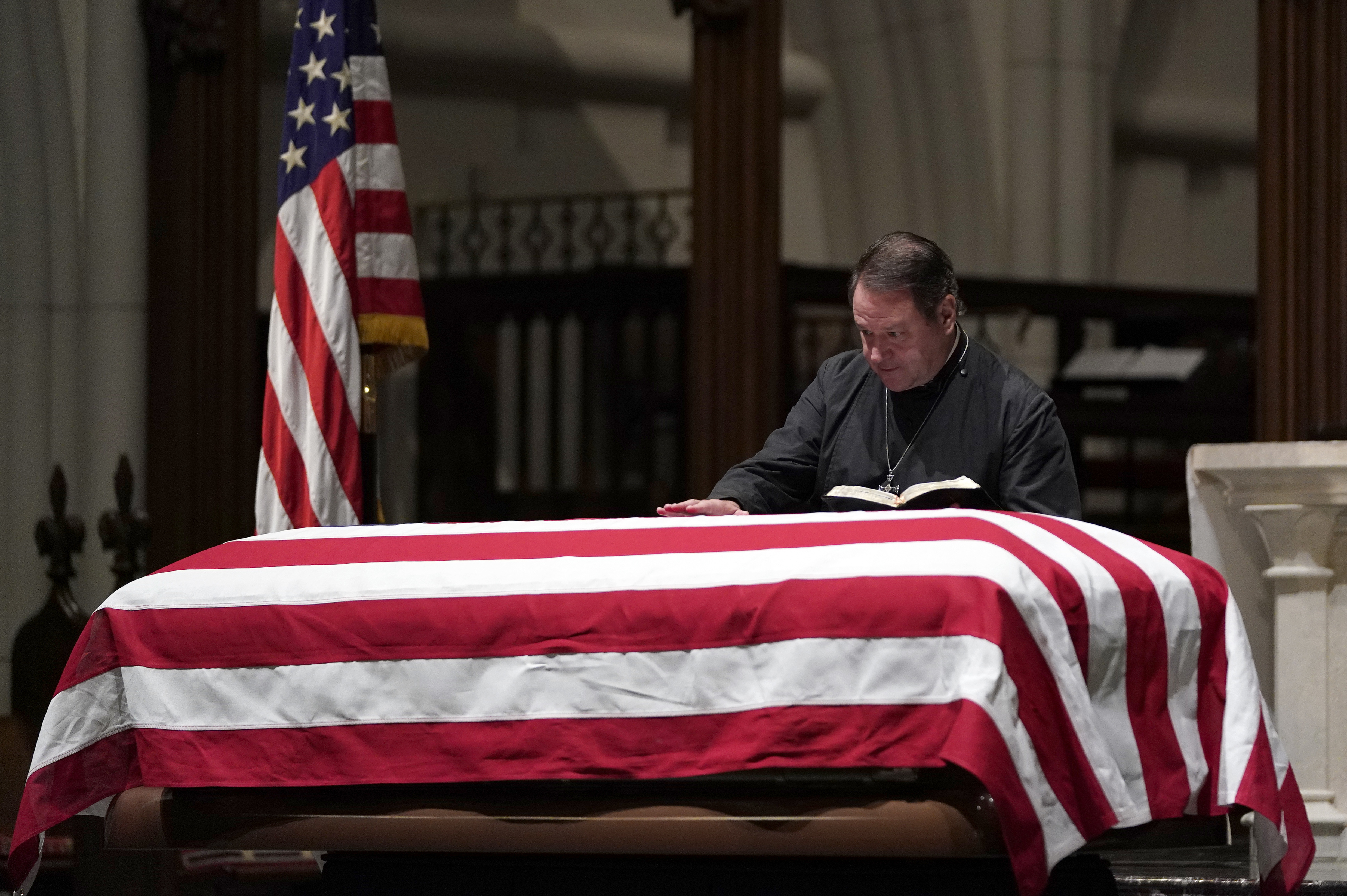 The Rev. Dr. Russell J. Levenson, Jr., rector of St. Martin's Episcopal Church, says a prayer over the casket of former President George H.W. Bush as he lies in repose at St. Martin's Episcopal Church Wednesday, Dec. 5, 2018, in Houston. (AP Photo/David J. Phillip, Pool) (AP Photo/David J. Phillip, Pool)
