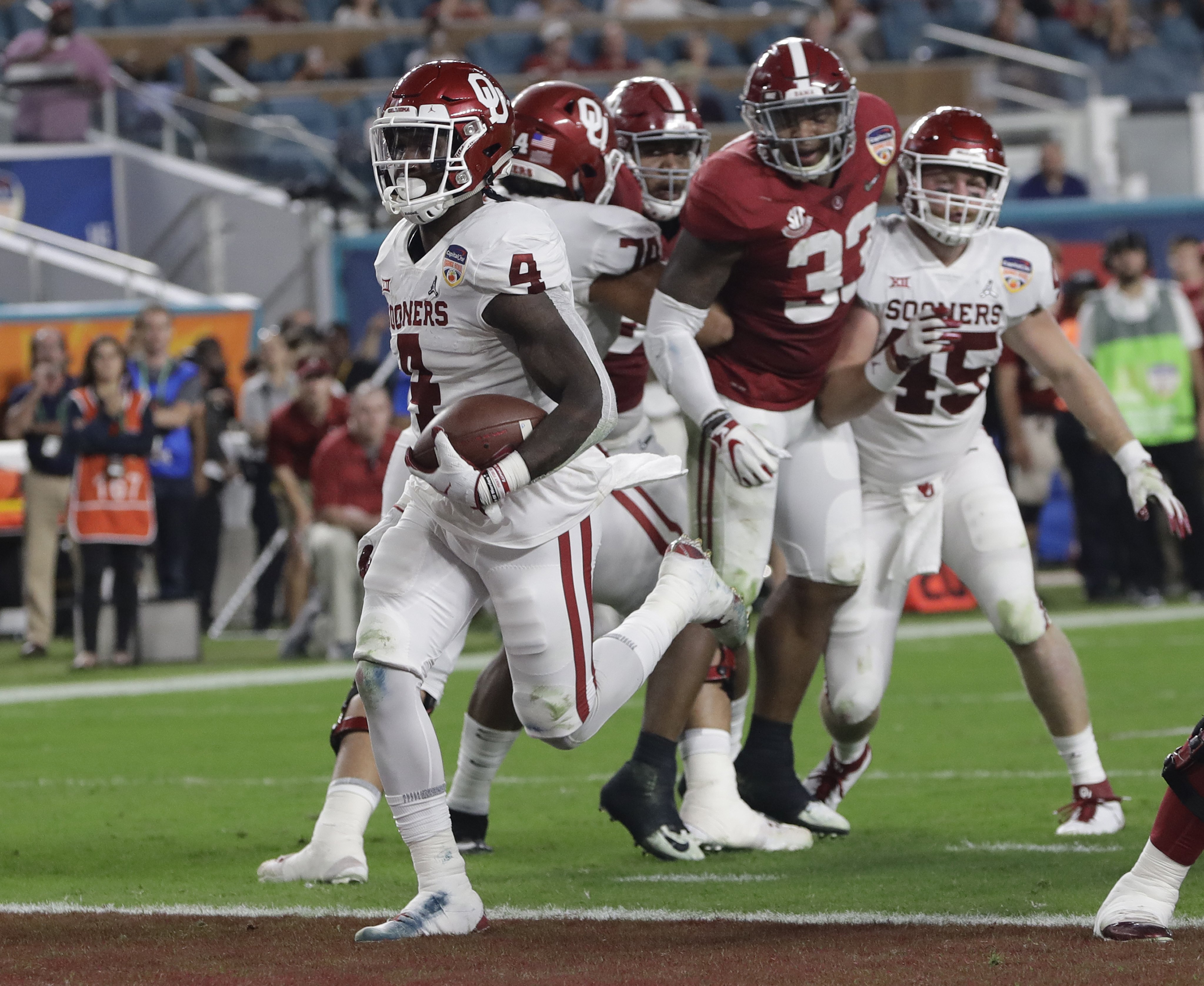 Oklahoma running back Trey Sermon (4) scores a touchdown, during the first half of the Orange Bowl NCAA college football game against Alabama, Saturday, Dec. 29, 2018, in Miami Gardens, Fla. (AP Photo/Lynne Sladky)