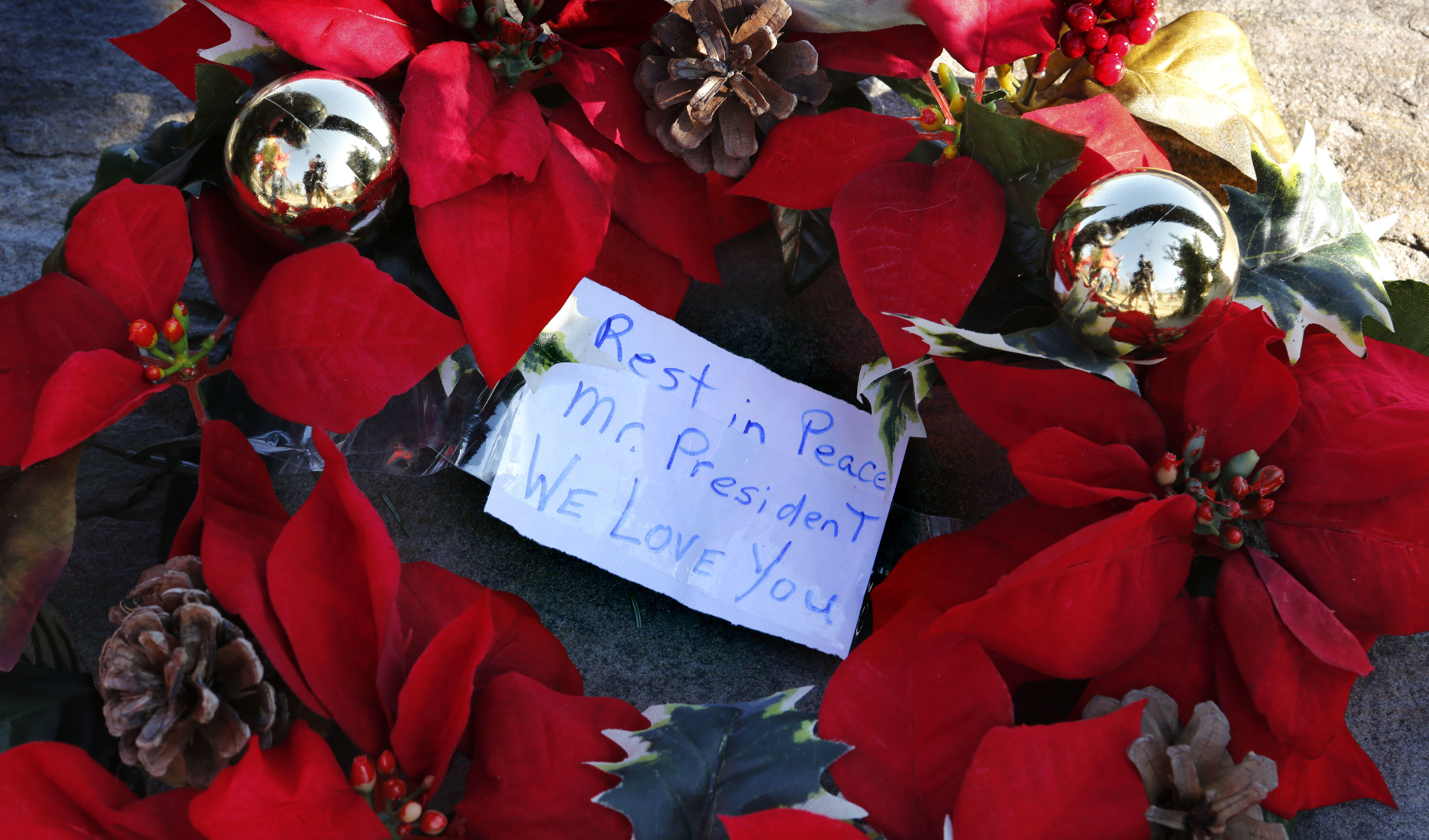 A wreath with a note to former President George H. W. Bush lay at a makeshift memorial across from Walker's Point, the Bush's summer home, Saturday, Dec. 1, 2018, in Kennebunkport, Maine. (AP Photo/Robert F. Bukaty)