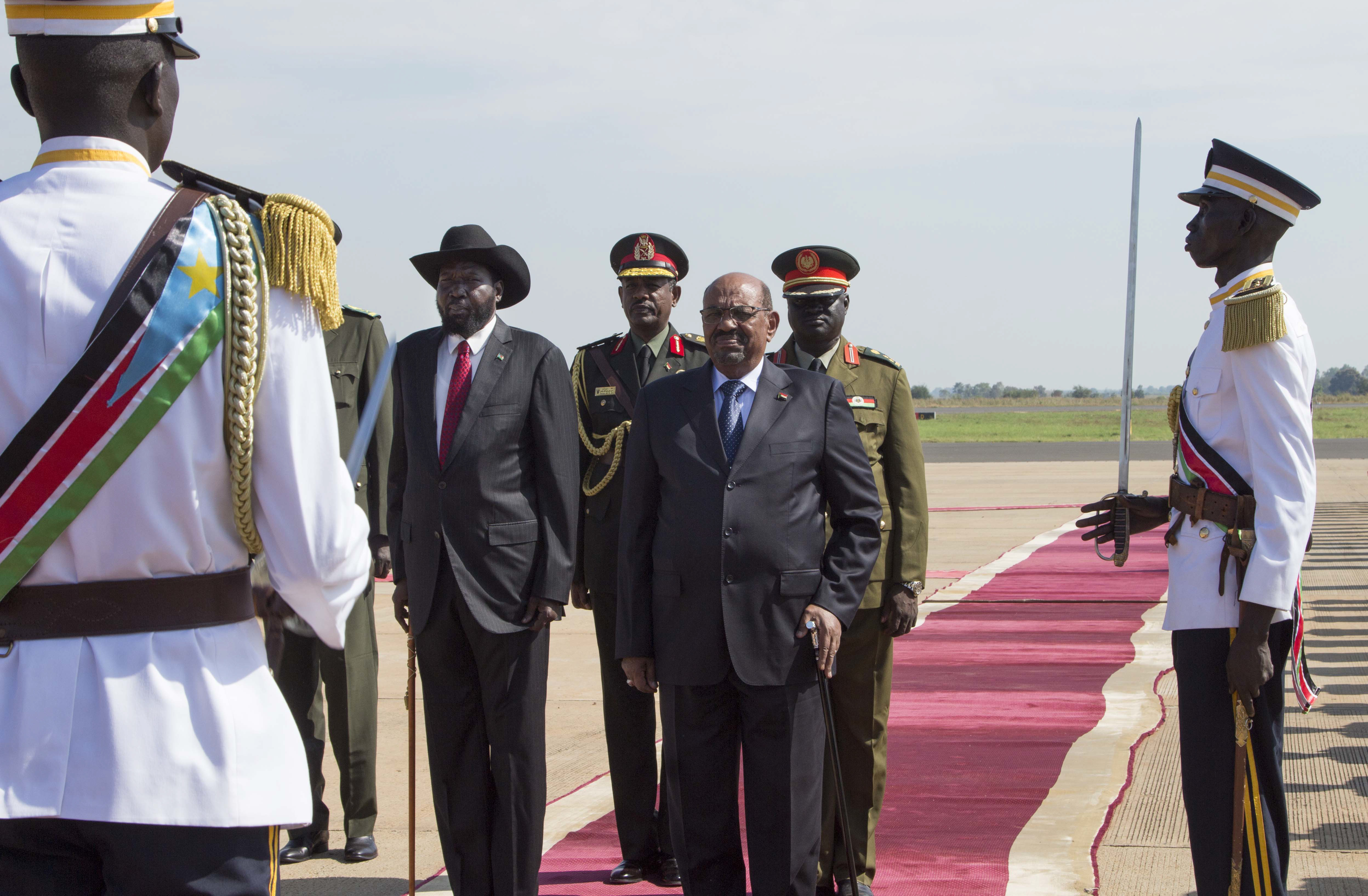 Sudan's President Omar al-Bashir, center, stands with South Sudan's President Salva Kiir, center left, during an arrival ceremony at the airport in Juba, South Sudan Wednesday, Oct. 31, 2018. For the first time since fleeing the war-torn country more than two years ago, South Sudan's opposition leader Riek Machar returned on Wednesday to take part in a nationwide peace celebration. (AP Photo/Bullen Chol)