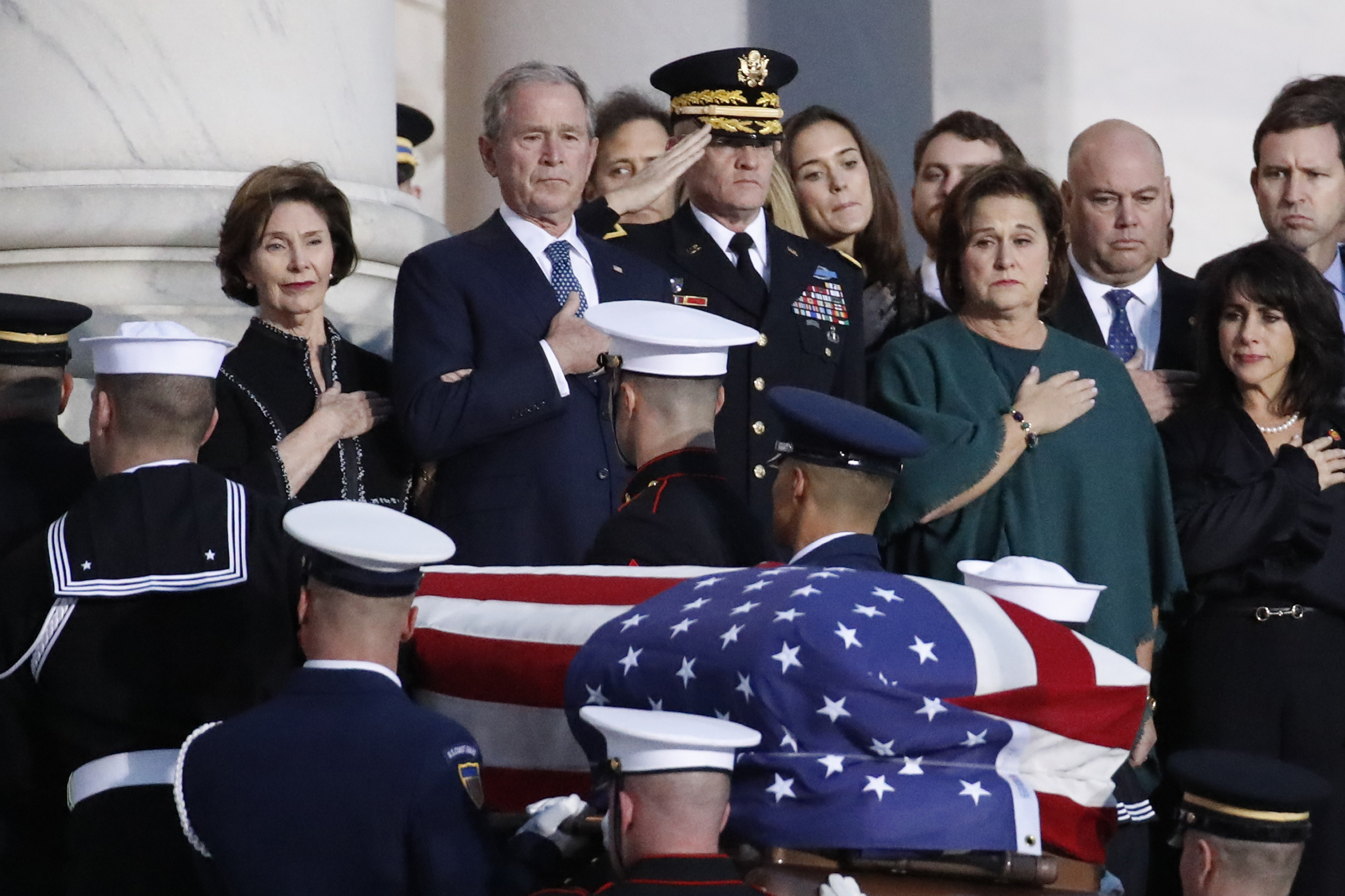 Former President George W. Bush, Laura Bush, left, and other family members watch as the flag-draped casket of former President George H.W. Bush is carried by a joint services military honor guard to lie in state in the rotunda of the U.S. Capitol, Monday, Dec. 3, 2018, in Washington.