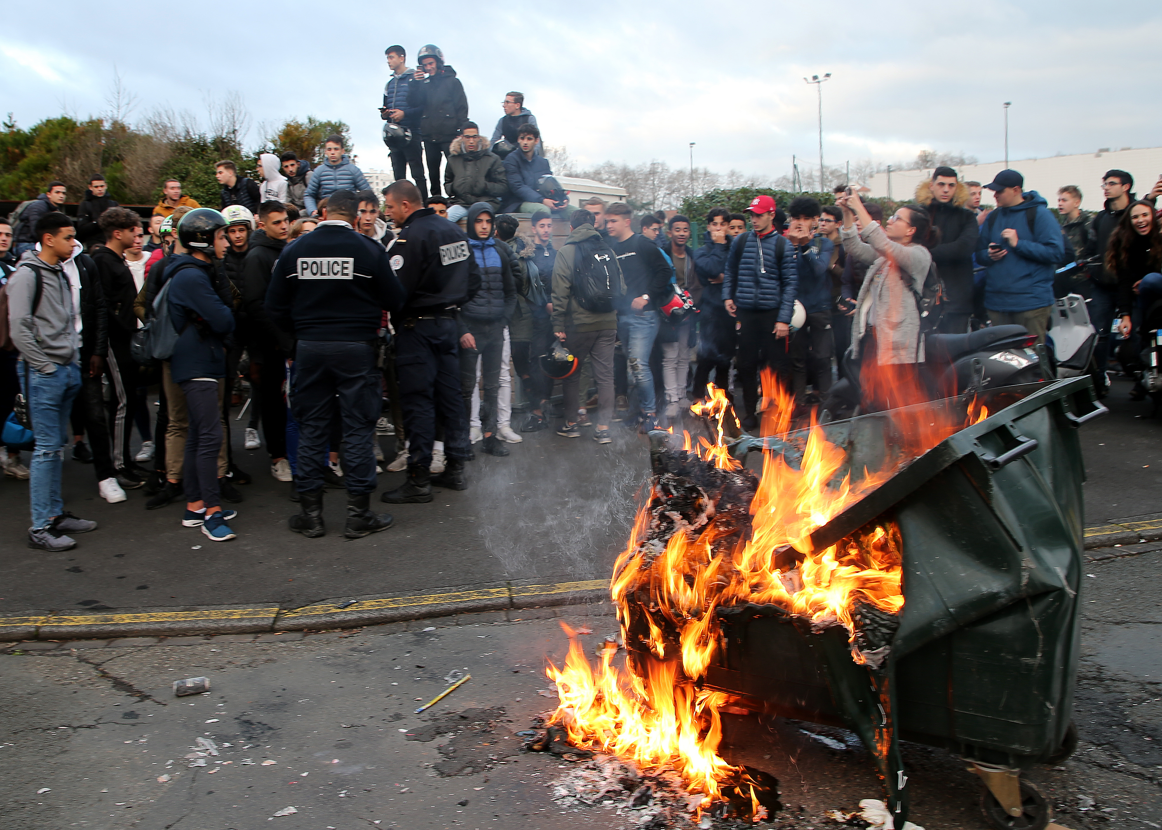 Students talk to police officers by a burning trash bin outside their school in Bayonne, southwestern France, Thursday, Dec.6, 2018. Protesting students are disrupting schools and universities Thursday, and drivers are still blocking roads around France, now demanding broader tax cuts and government aid. (AP Photo/Bob Edme)