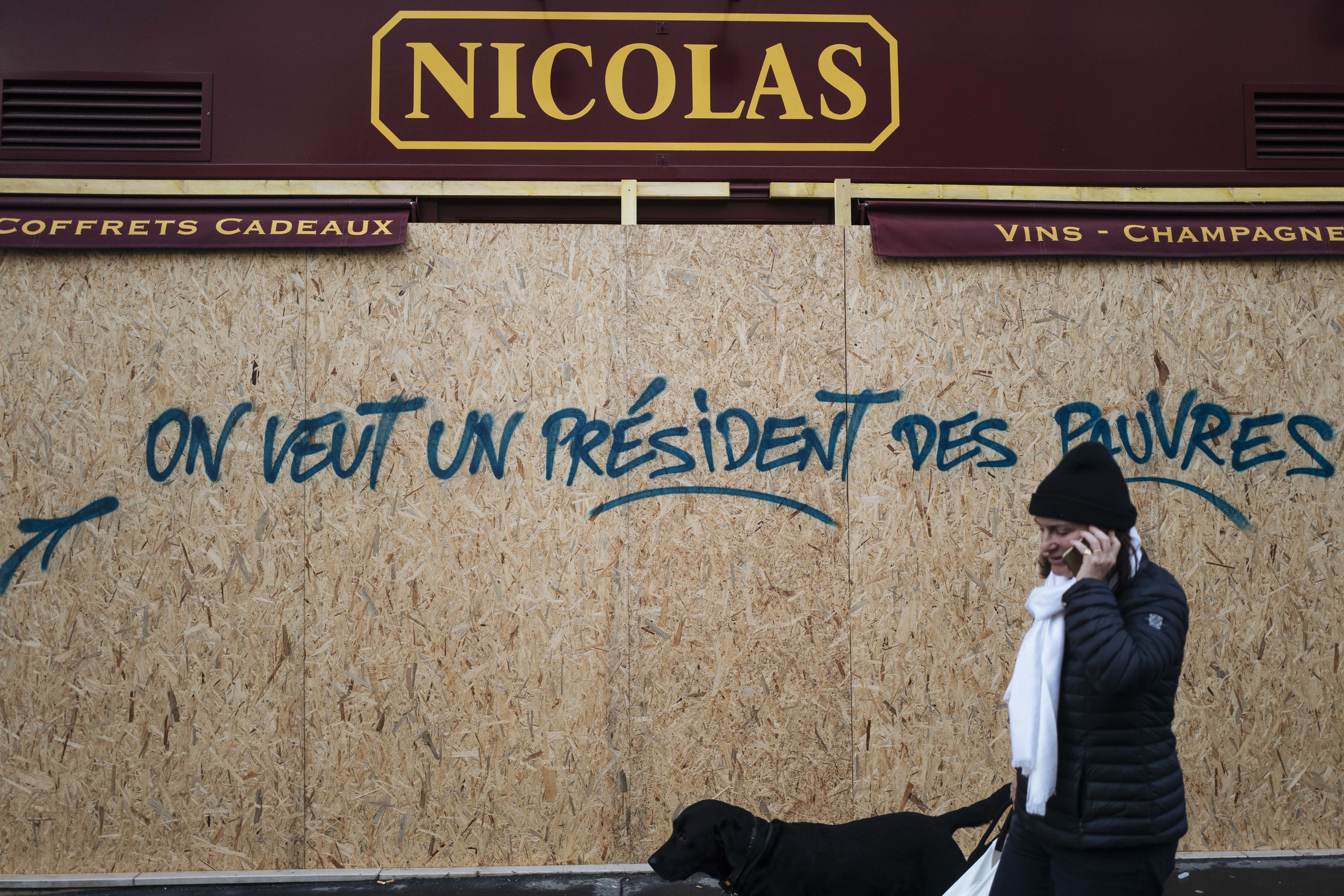 FILE - In this Sunday, Dec. 2, 2018 file picture, a woman walks past a graffiti on a boarded up wine shop reading 'We want a president for the poor', near the Arc de Triomphe, in Paris, France. One year and a half after he came into power, Macron is facing violent protests over rising taxes. (AP Photo/Kamil Zihnioglu, File)