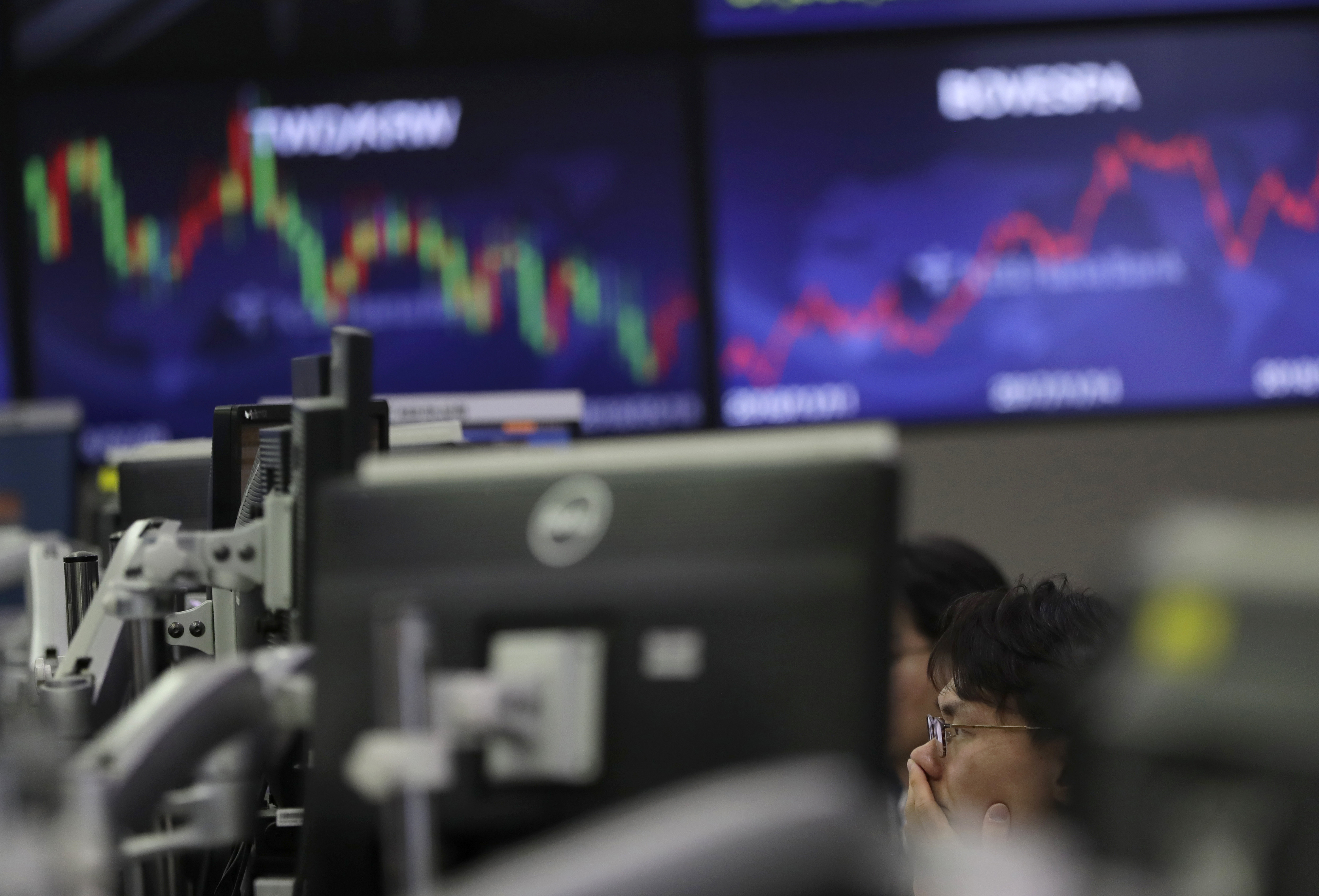 A currency trader watches computer monitors at the foreign exchange dealing room in Seoul, South Korea, Wednesday, Nov. 21, 2018. Asian markets fell on Wednesday after a trade dispute between the U.S. and China stalled a weekend meeting, dimming hopes that it could be resolved once their leaders meet. (AP Photo/Lee Jin-man)