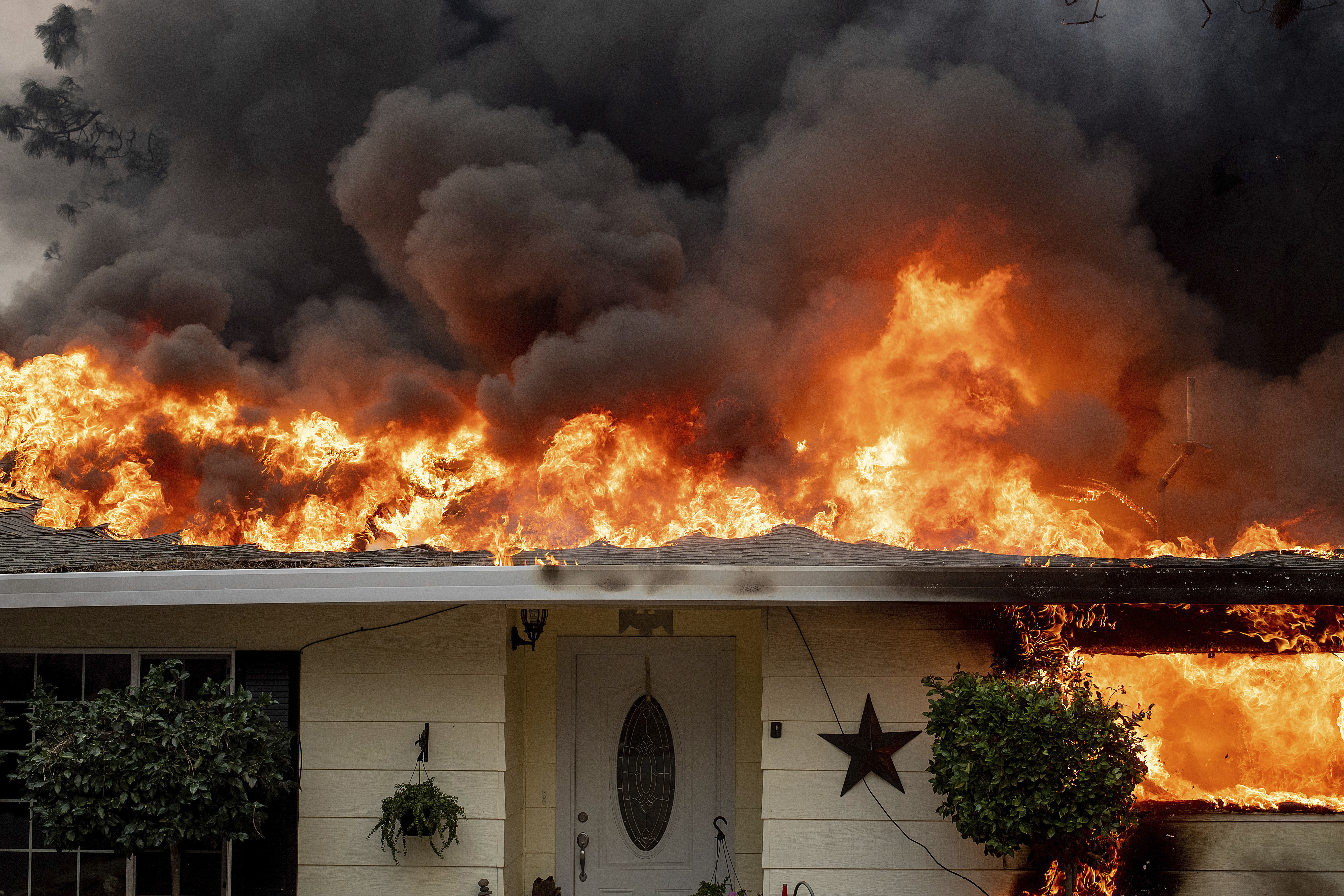 Flames consume a home as the Camp Fire tears through Paradise, Calif., on Thursday, Nov. 8, 2018. A California fire official says a fast-moving wildfire in Northern California has destroyed structures and injured civilians. (AP Photo/Noah Berger)