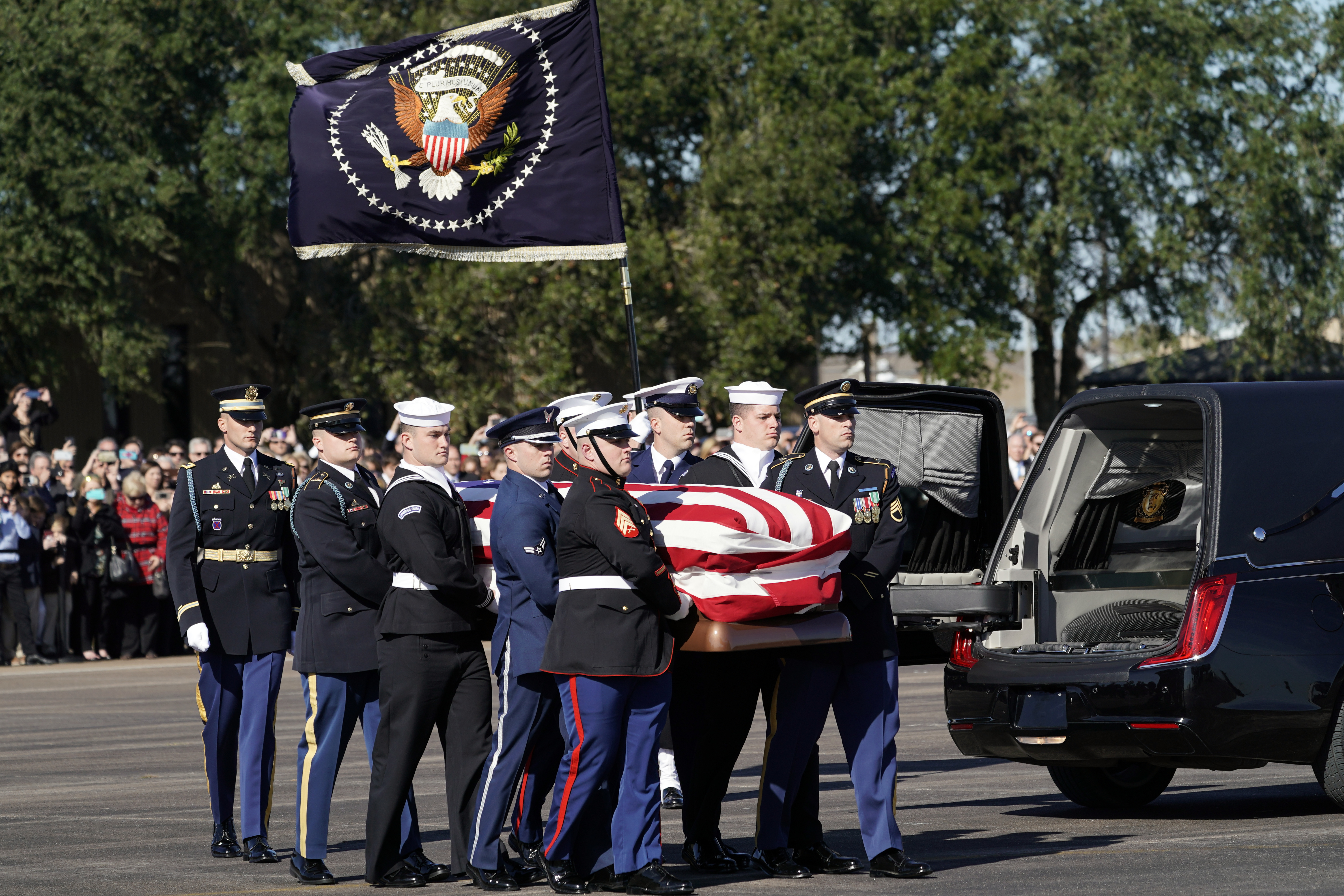 The flag-draped casket of former President George H.W. Bush is carried by a joint services military honor guard Monday, Dec. 3, 2018, at Ellington Field in Houston. (AP Photo/David J. Phillip, Pool)