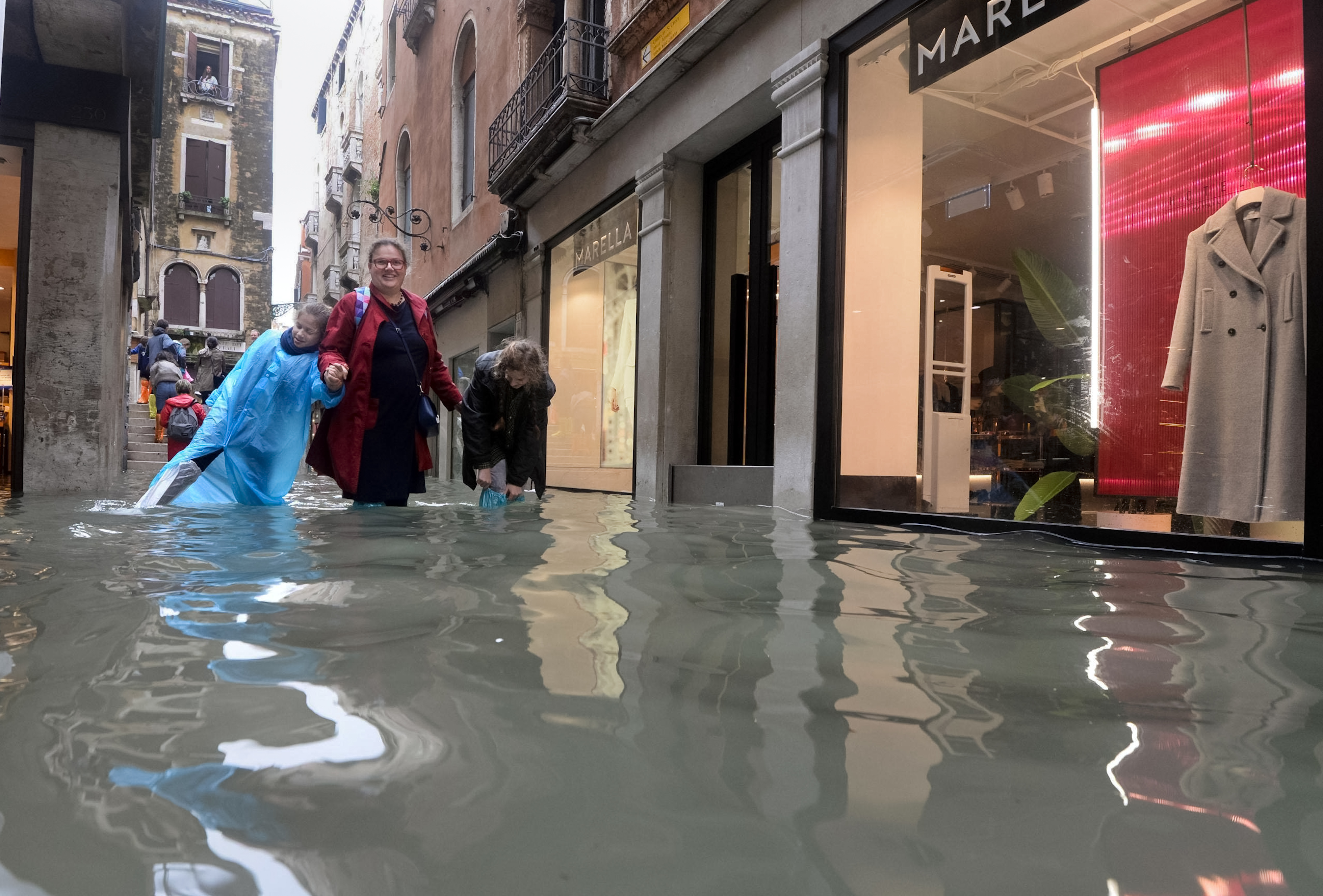People walk in a flooded street of Venice, Italy, Monday, Oct. 29, 2018, as, according to city officials, 70 percent of the lagoon city has been flooded by waters rising 156 centimeters (more than 61.41 inches) above sea level. Venice frequently floods when high winds push in water from the lagoon, but Monday's levels are exceptional. (Andrea Merola/ANSA via AP)