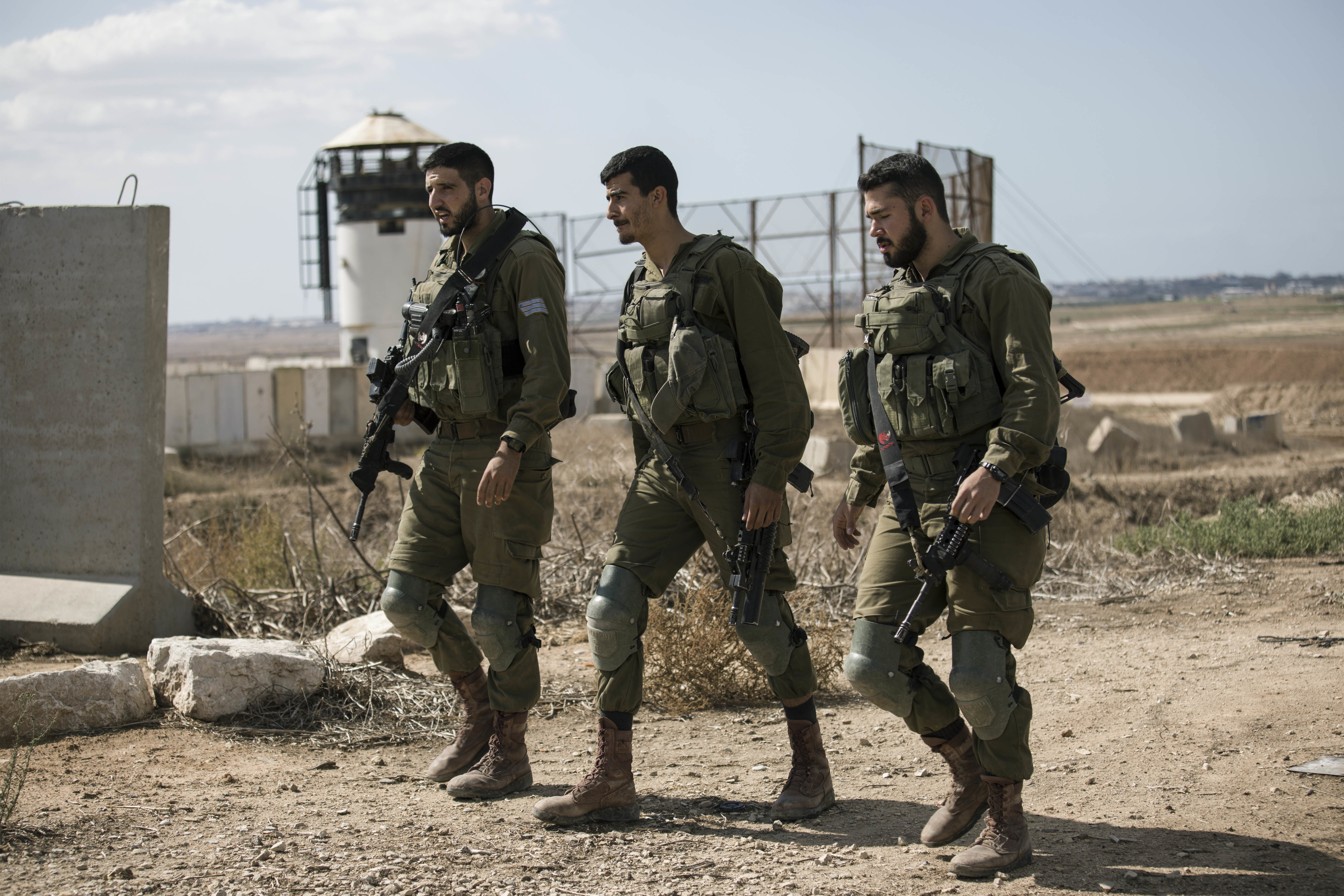 Israeli soldiers walk by an outpost near the Gaza Strip border, Saturday, Oct. 27, 2018. The Israeli military has struck dozens of targets across the Gaza Strip in response to heavy rocket fire and threatened to expand its air campaign to Syria after accusing Iranian forces in Damascus of orchestrating the rocket attacks. (AP Photo/Tsafrir Abayov)