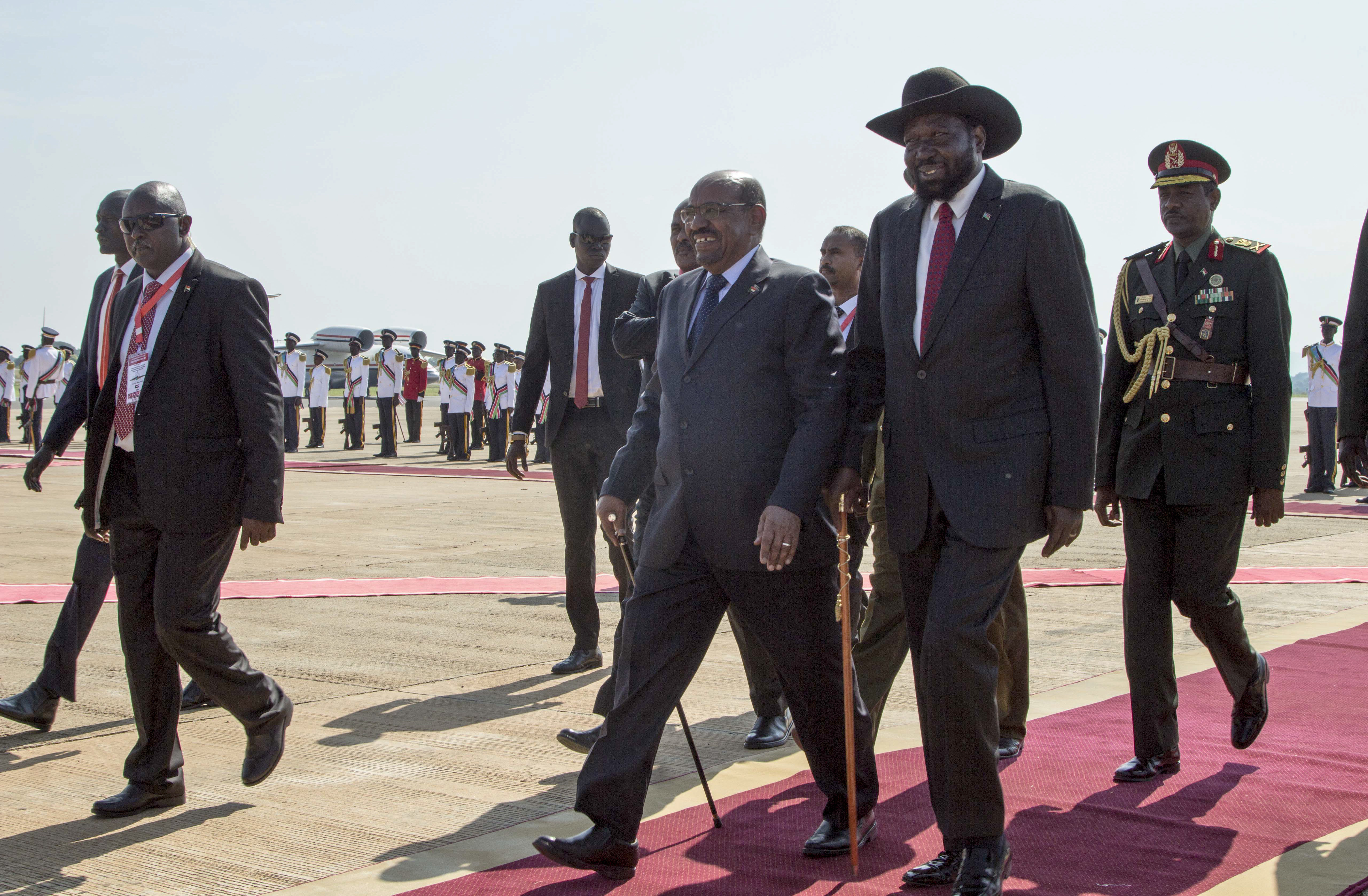 Sudan's President Omar al-Bashir, center, walks with South Sudan's President Salva Kiir, center right, as he arrives at the airport in Juba, South Sudan Wednesday, Oct. 31, 2018. For the first time since fleeing the war-torn country more than two years ago, South Sudan's opposition leader Riek Machar returned on Wednesday to take part in a nationwide peace celebration. (AP Photo/Bullen Chol)