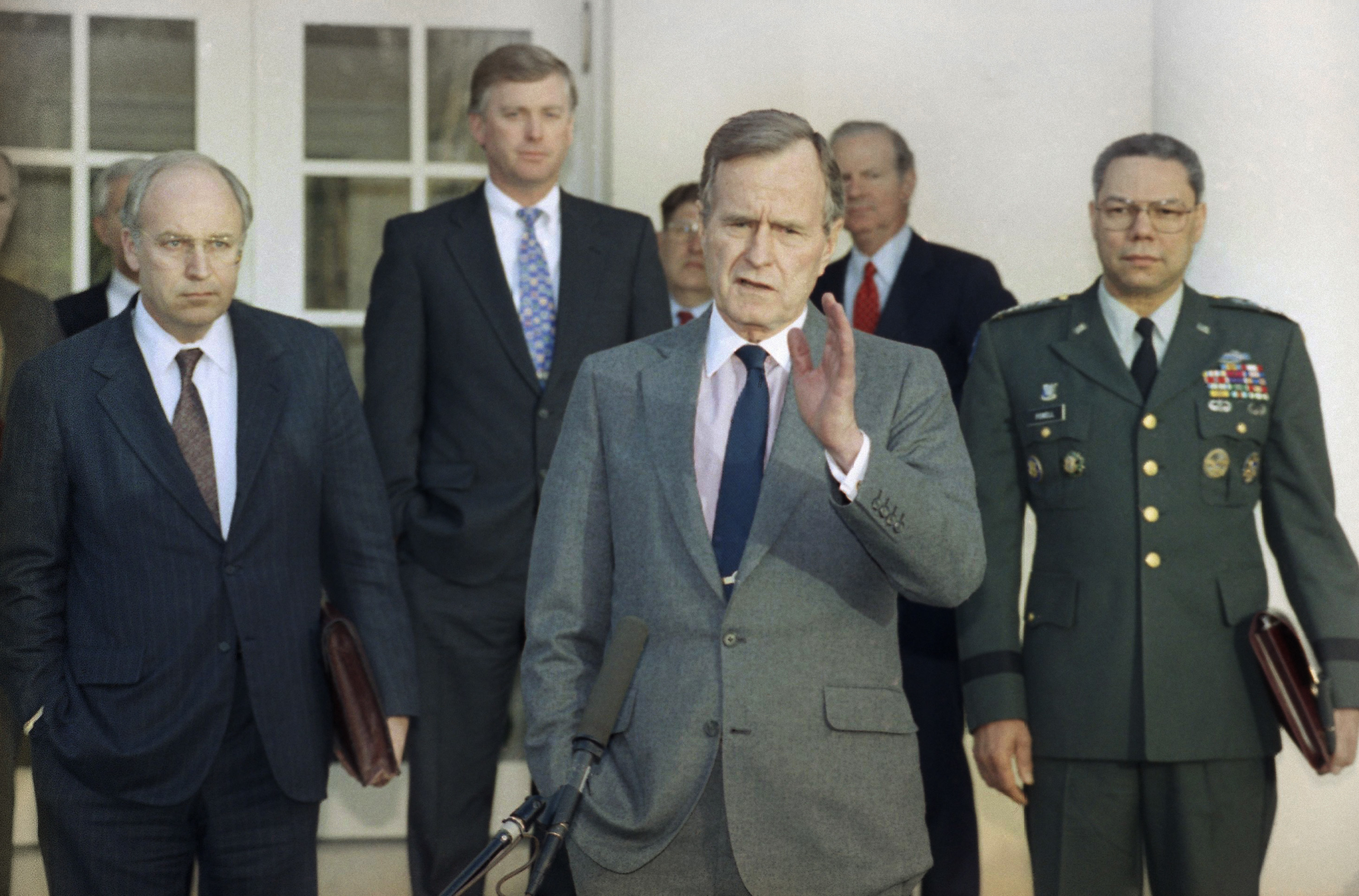 In this Feb. 11, 1991, photo, President George H.W. Bush talks to reporters in the Rose Garden of the White House after meeting with top military advisors to discuss the Persian Gulf War. From left are, Defense Secretary Dick Cheney, Vice President Dan Quayle, White House Chief of Staff John Sununu, the president, Secretary of State James A. Baker III, and Joint Chiefs Chairman Gen. Colin Powell. (AP Photo/Ron Edmonds, File)