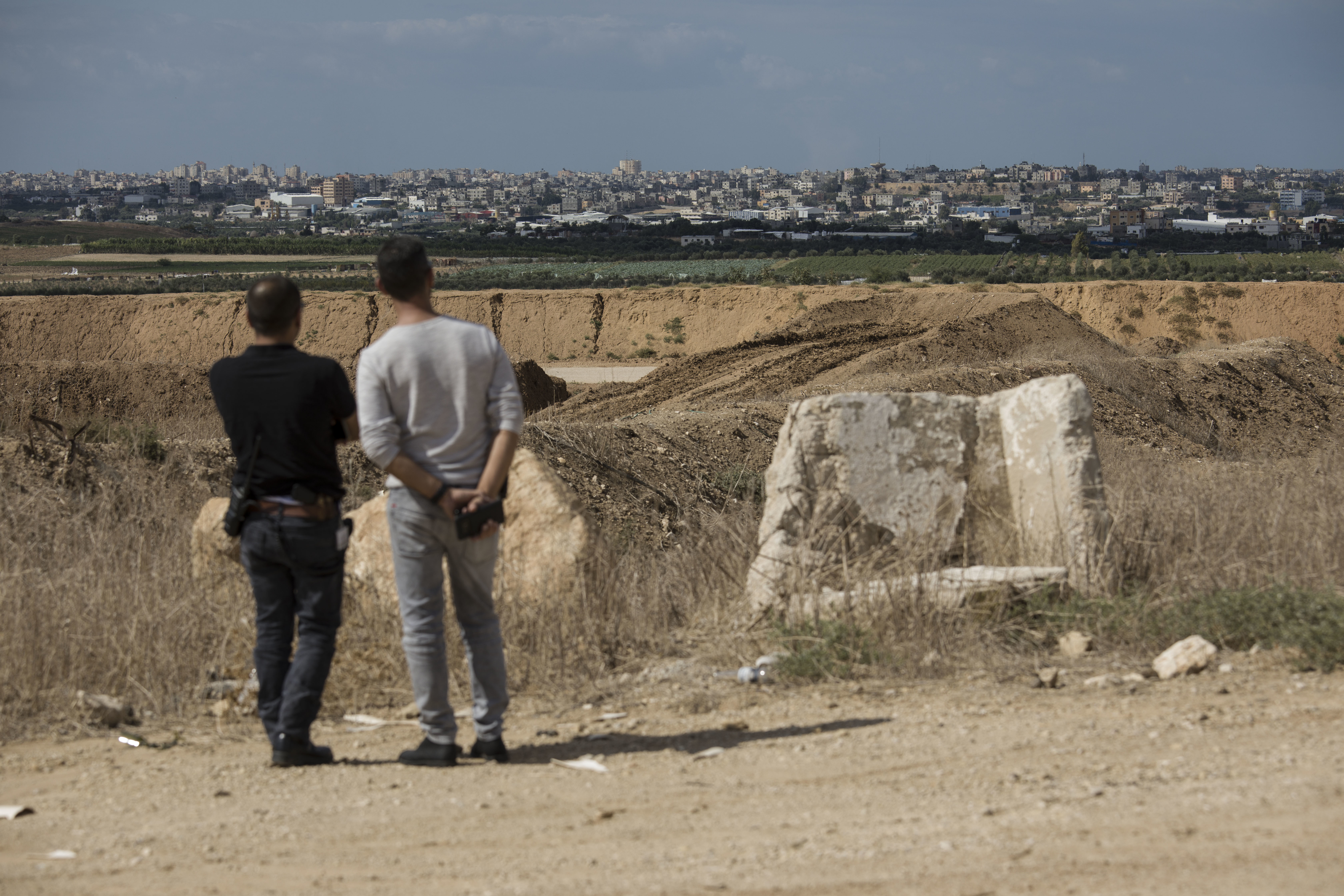 Israelis look at the Gaza Strip border, Saturday, Oct. 27, 2018. The Israeli military has struck dozens of targets across the Gaza Strip in response to heavy rocket fire and threatened to expand its air campaign to Syria after accusing Iranian forces in Damascus of orchestrating the rocket attacks. (AP Photo/Tsafrir Abayov)